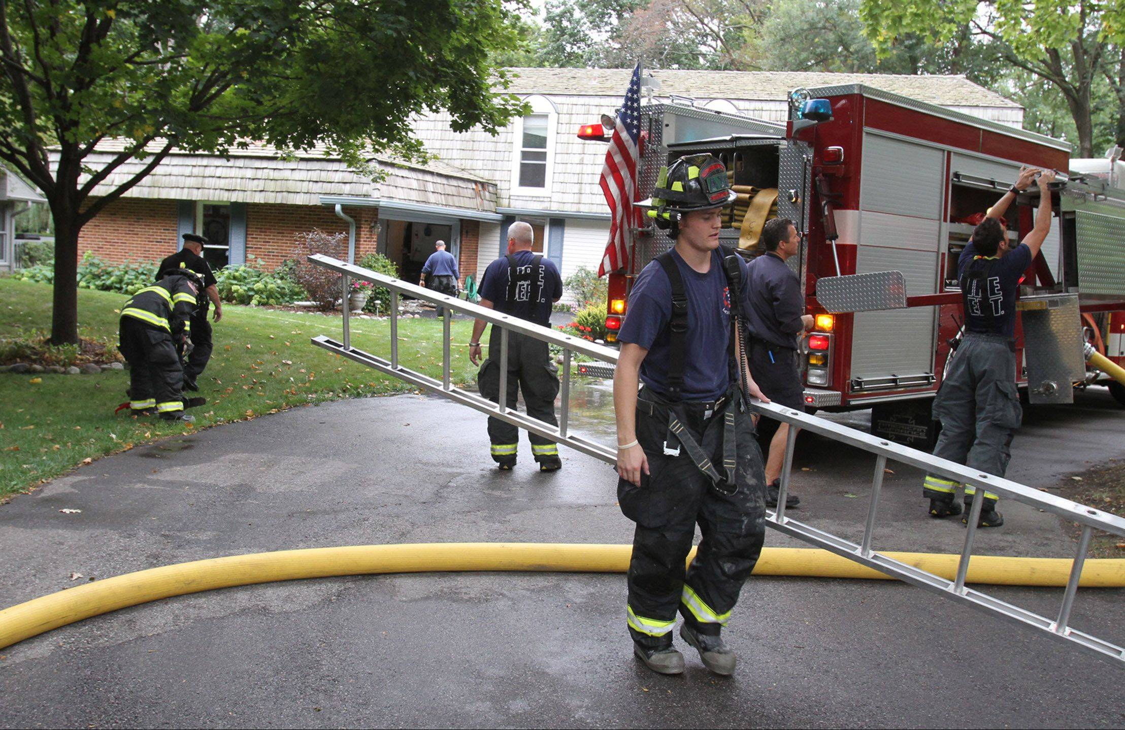 Rolling Meadows firefighters retrieve gear after a house fire on the 0-99 block of Fieldstone Road in Rolling Meadows on Wednesday.