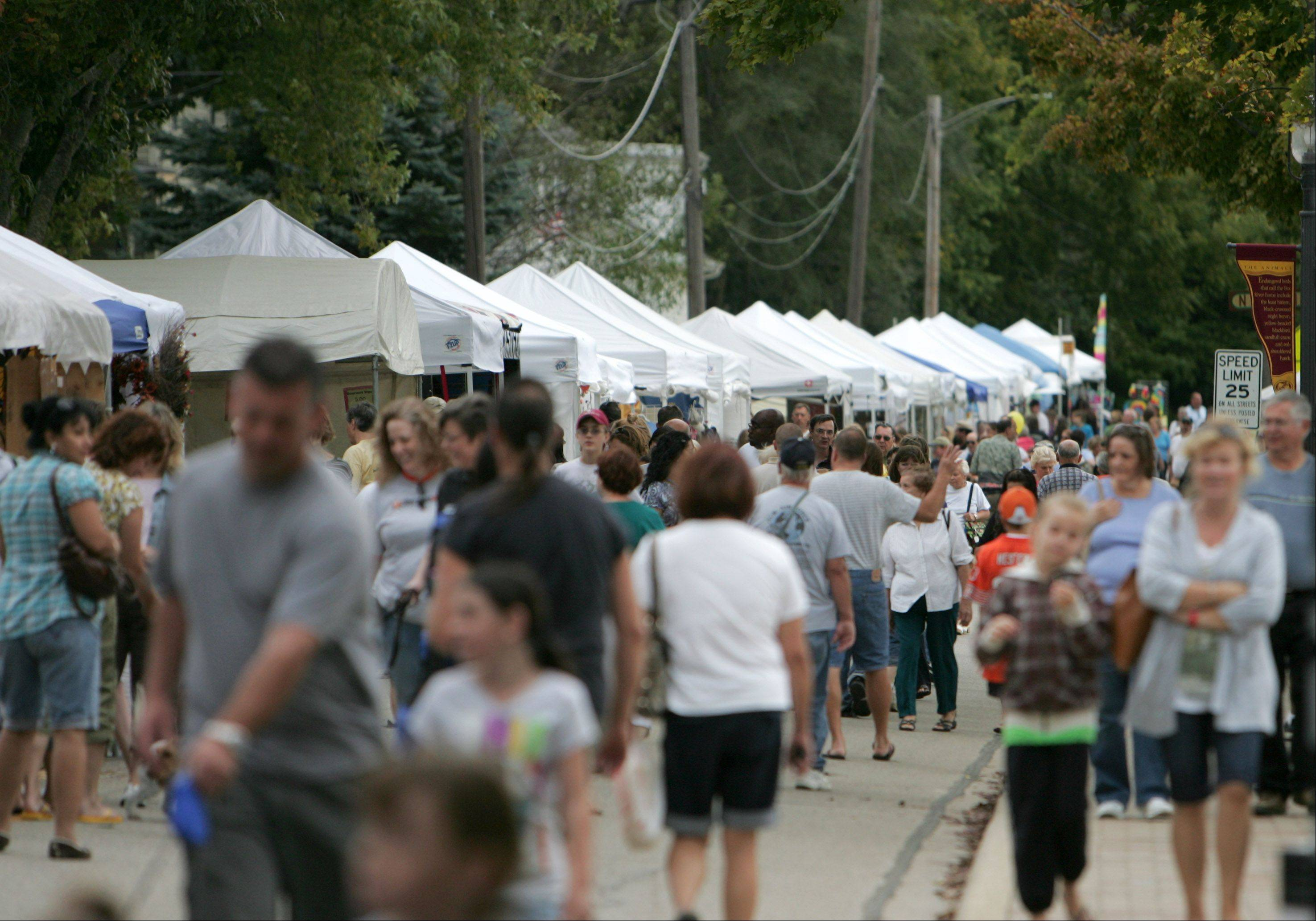 Visitors gather on the Riverwalk for an arts and crafts show during a previous West Dundee Heritage Fest. This year's festival starts today and runs through Sunday.