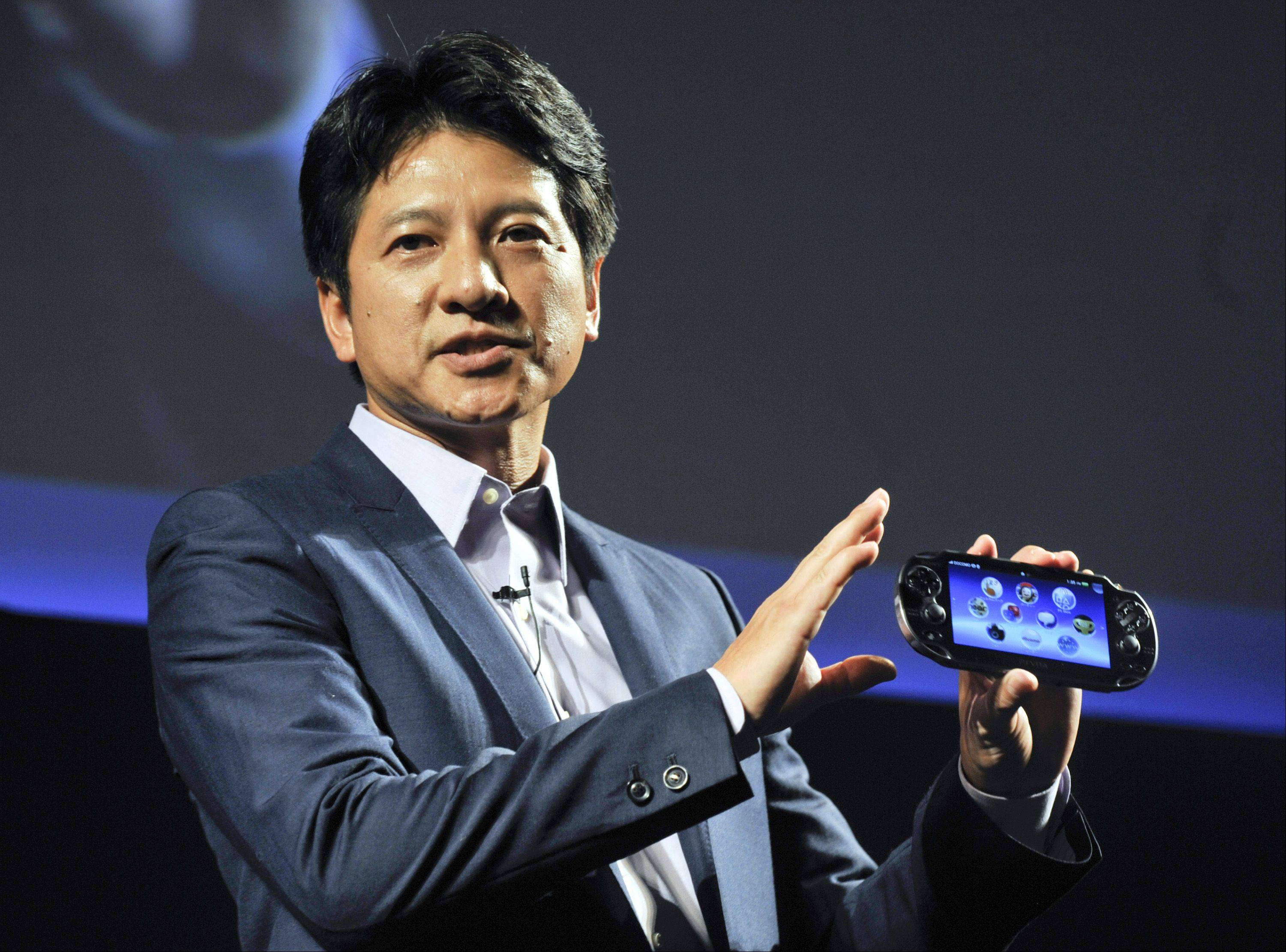 Hiroshi Kawano, president of Sony Computer Entertainment Japan, displays the PlayStation Vita portable video game player as he speaks at a news conference in Tokyo on Wednesday.