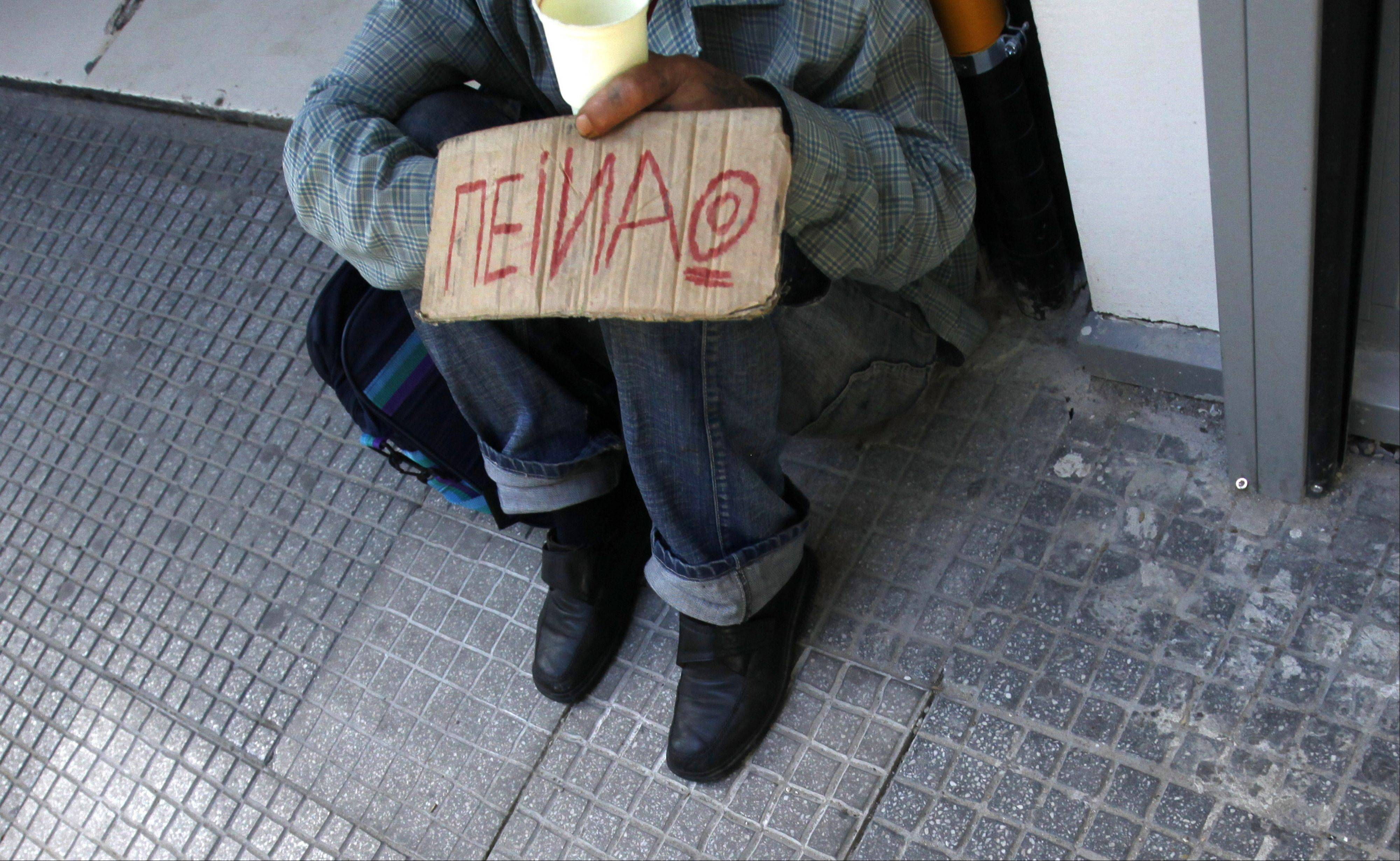 A beggar holds a poster reading, �I�m hungry,� in Thessaloniki Wednesday. Greek leader George Papandreou has promised to greatly speed up public sector cuts and impose more blanket taxation to plug budget shortfalls.