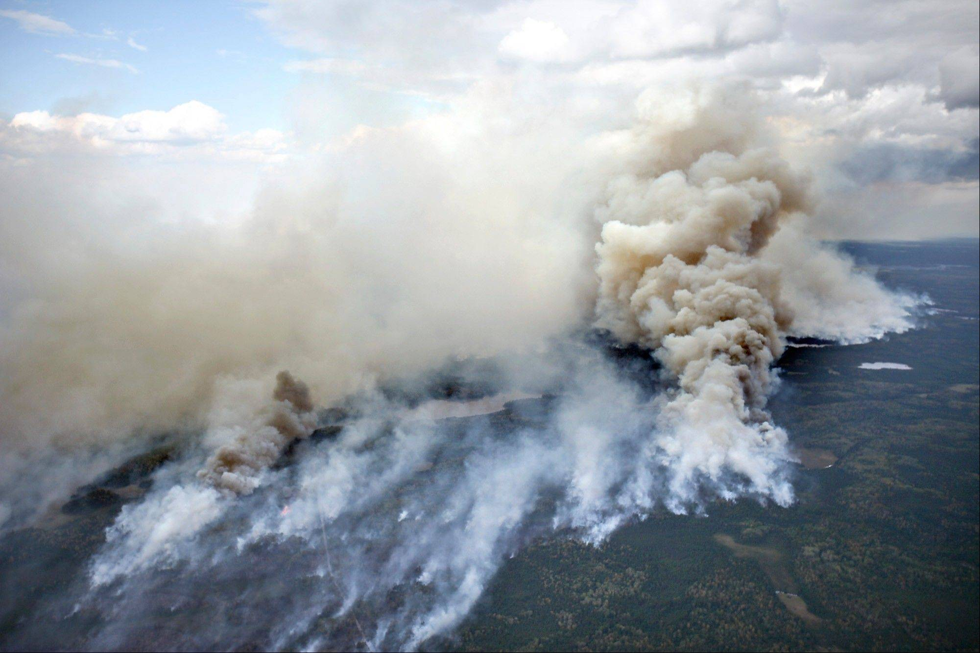 In this aerial photo, an area of the Pagami Creek wildfire shows active burning and creates a large smoke plume on Tuesday in the Boundary Waters Canoe Area Wilderness in Northeastern Minnesota. The haze from the fire was heavy enough that some people reported burning eyes and difficulty breathing in the Chicago area, 600 miles south of the forest fire, the National Weather Service said.