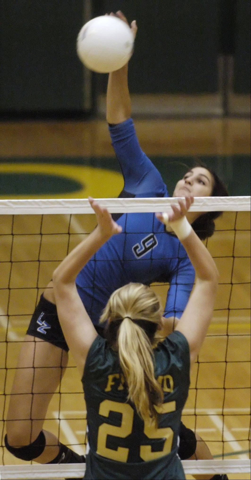 Lake Zurich�s Amanda Orchard leaps for a kill in front of Fremd�s Lane Hindenburg.