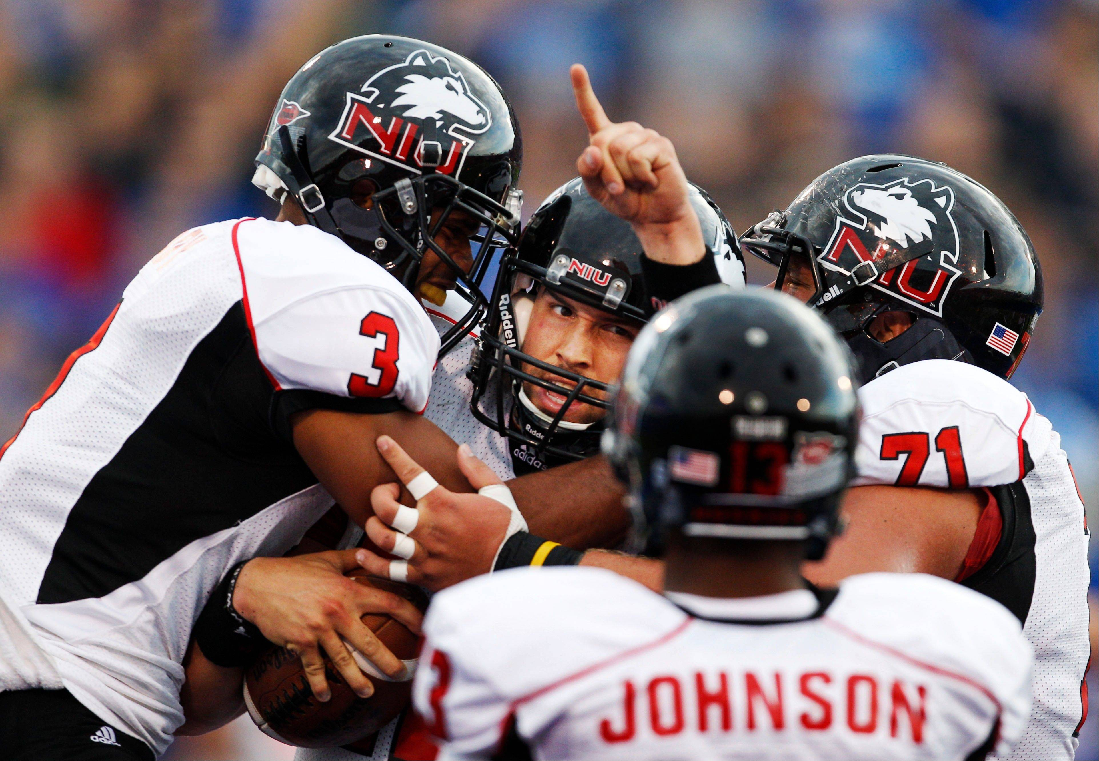 Northern Illinois quarterback Chandler Harnish, middle, celebrates a touchdown with teammates DeMarcus Grady (3) and Scott Wedige (71) Saturday during the first half against Kansas in Lawrence, Kan.