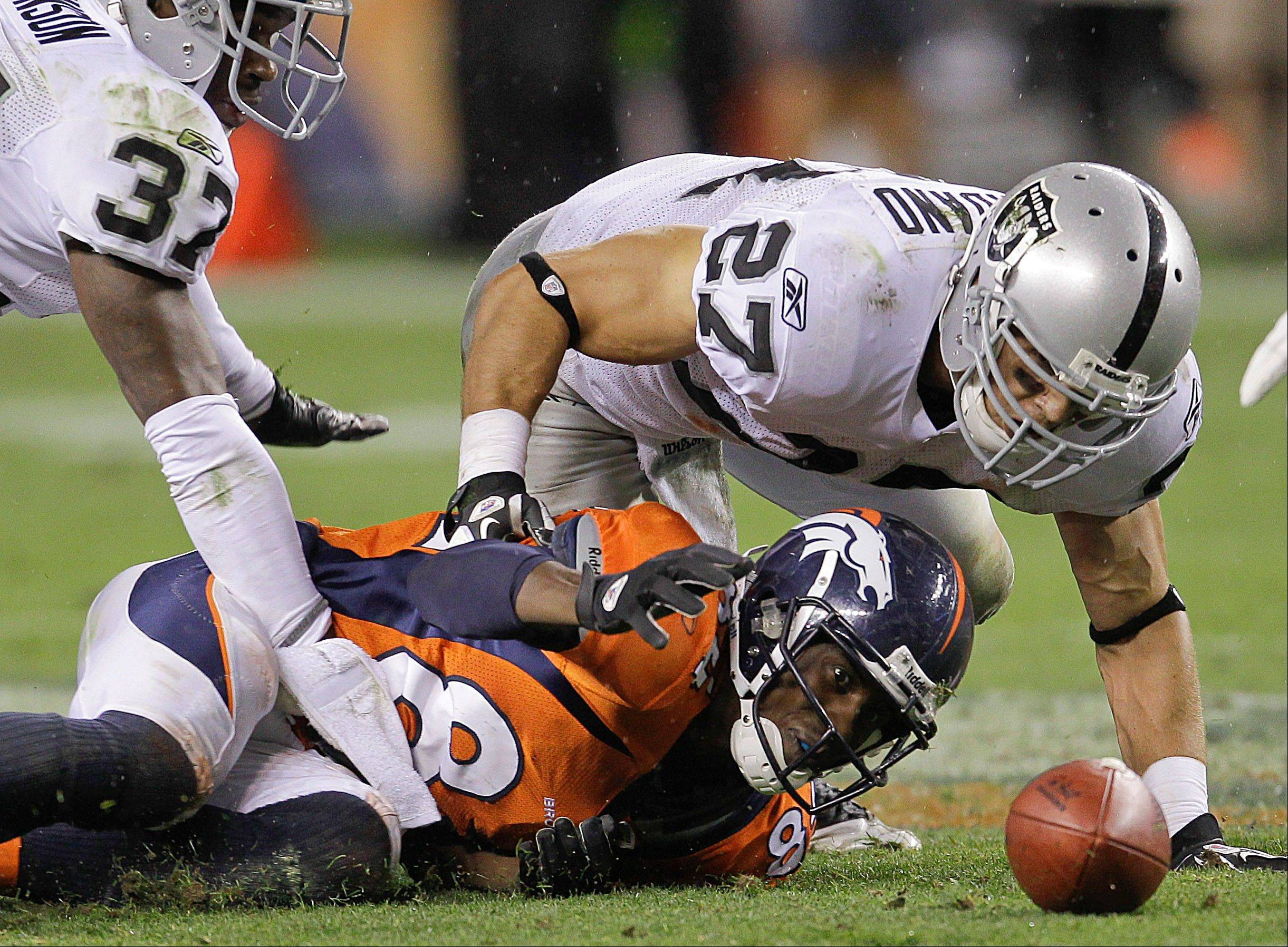 Denver Broncos wide receiver Brandon Lloyd, and Oakland Raiders defensive backs Matt Giordano (27) and Chris Johnson reach for the ball that Lloyd fumbled in the fourth quarter Monday night in Denver. The Raiders won 23-20.