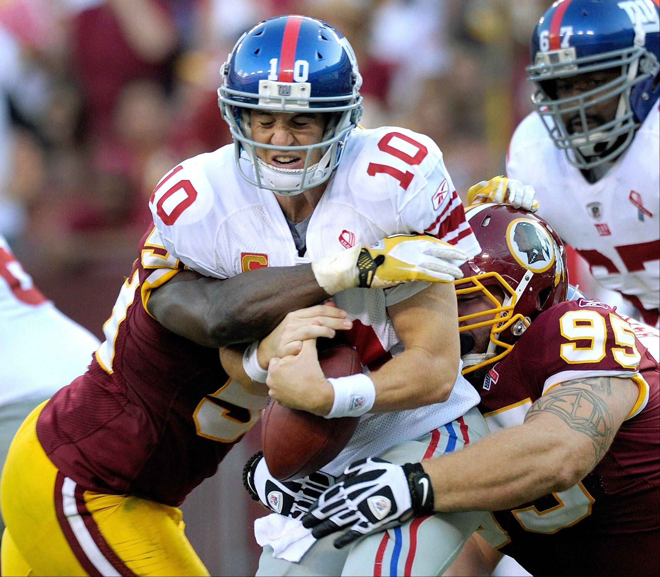 New York Giants quarterback Eli Manning is sacked by Washington Redskins linebacker London Fletcher, left, and nose tackle Chris Neild, right, during the second half Sunday.