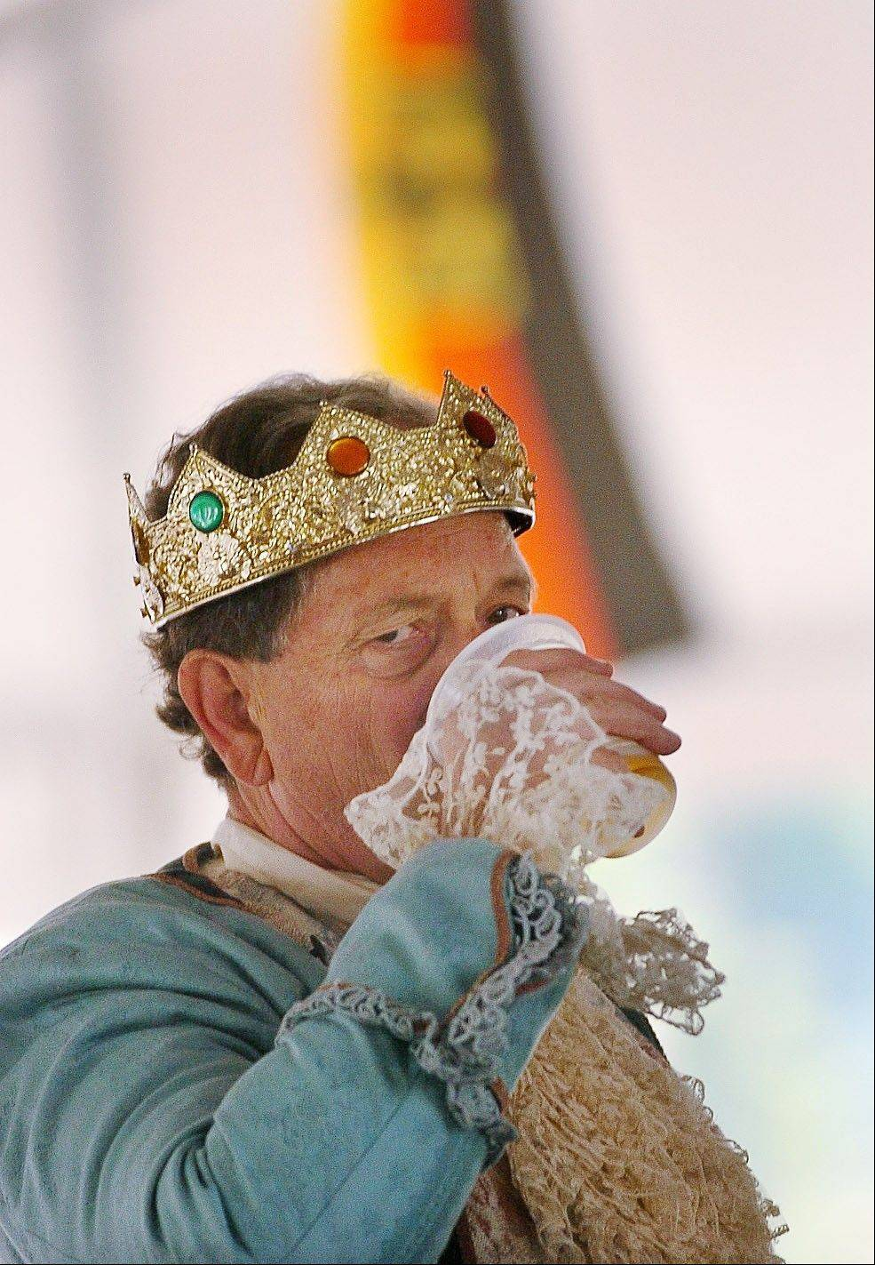 Jim McLin, the Grandfather King of the 2010 Oktoberfest, hoists a beer in front of a German flag.