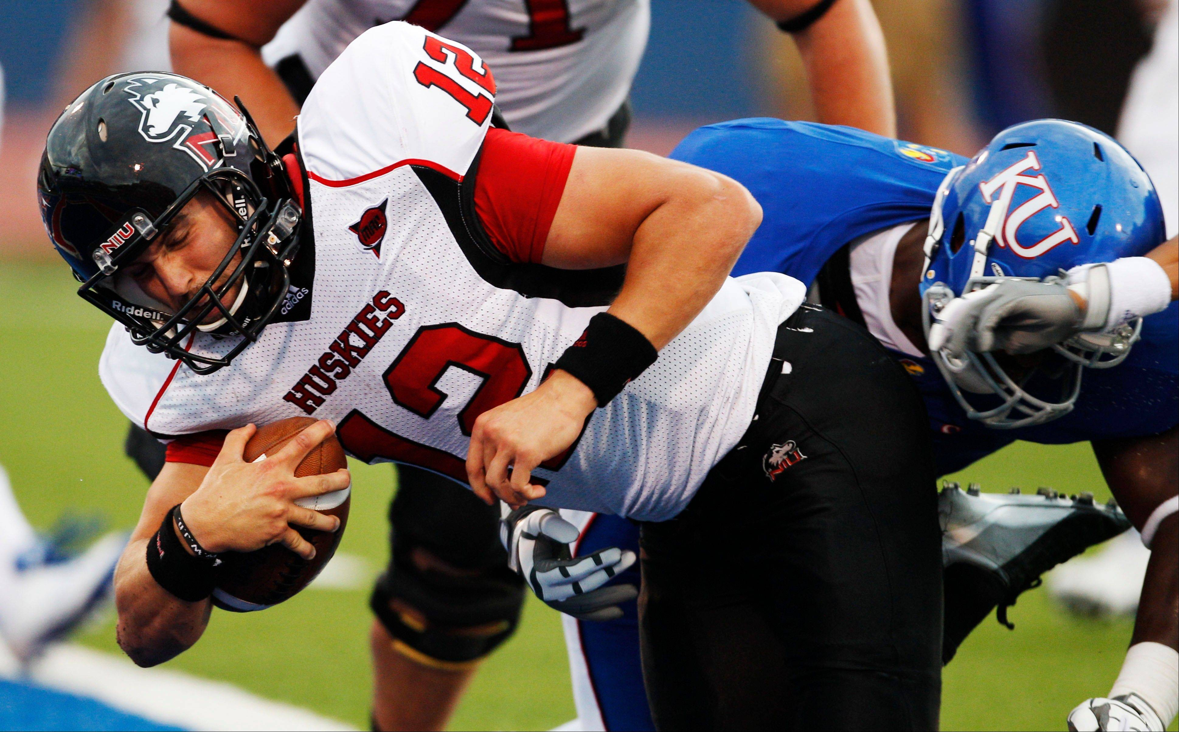 Northern Illinois quarterback Chandler Harnish gets past Kansas safety Bradley McDougald, right, for a touchdown Saturday during the first half in Lawrence, Kan.
