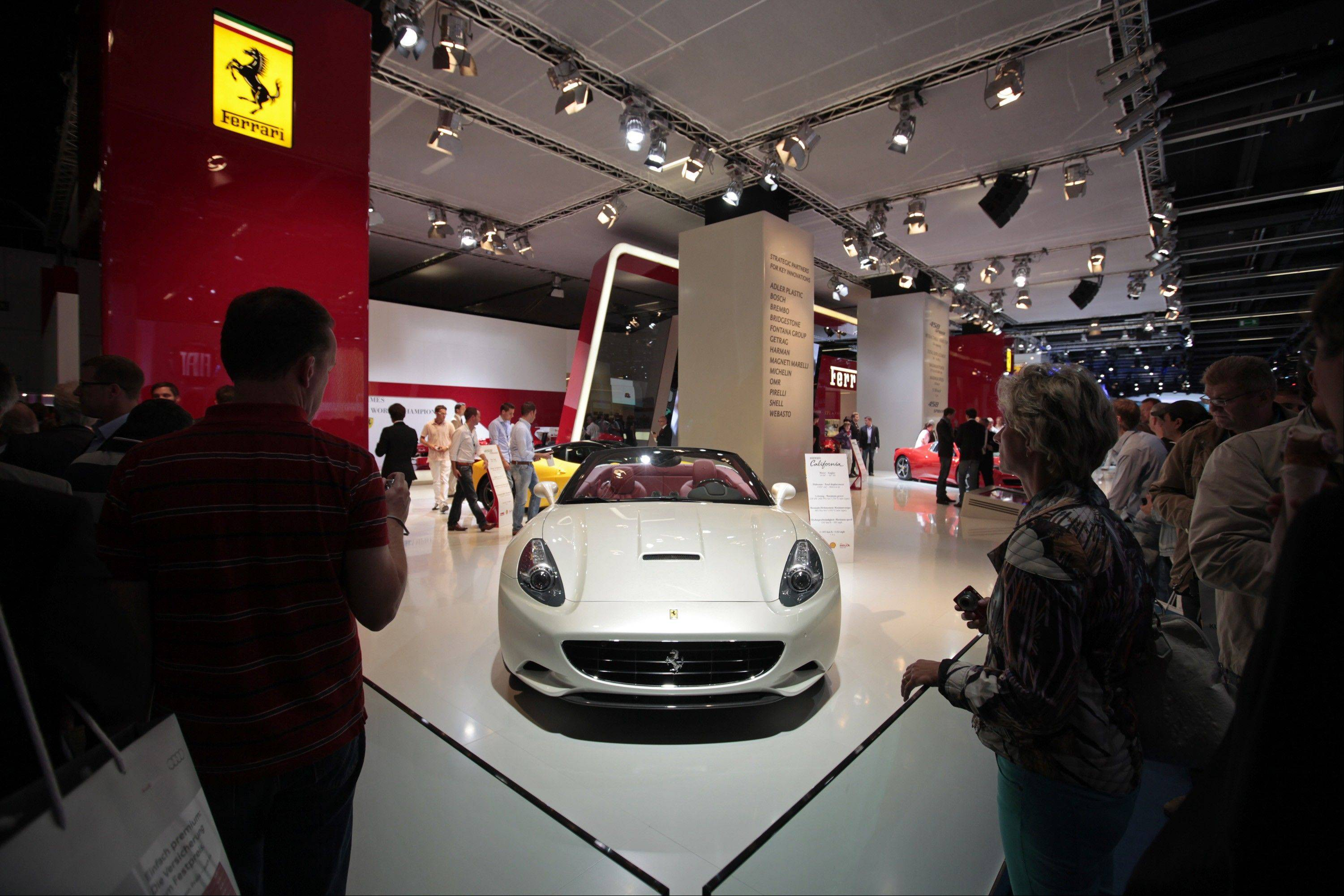 Visitors look at a Ferrari SpA California automobile during the Frankfurt Motor Show, in Frankfurt, Germany Thursday, Sept. 15.