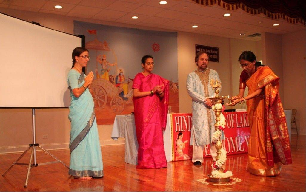 Speakers Kristen Mandziuk, left, Maya Jairam, Dr. Richard Benkin and Bhavna Shinde Hurley light the lamp at the Third Hinduism Summit in Chicago held at the Hindu Temple of Lake County in Grayslake.