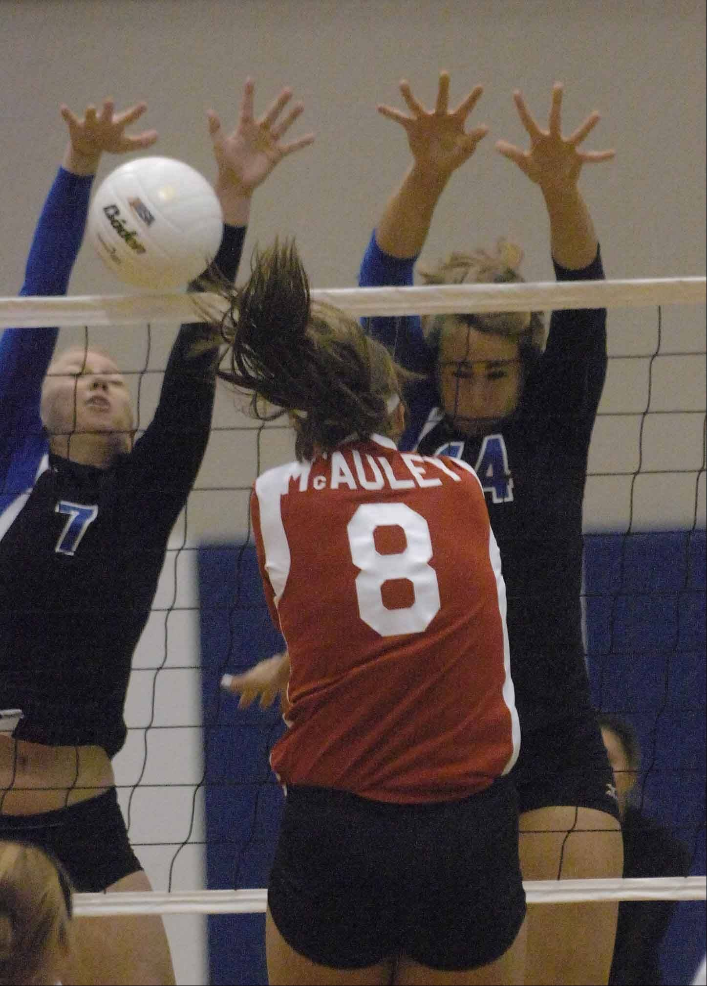 PAUL MICHNA/Pmichna@dailyherald.com Hayley Gable,left, and Daiva Wisebothof St. Francis block a shot by Ryann Arundel of Mother McAuley. this took place during the Mother McAuley at St. Francis girls volleyball game Thursday.