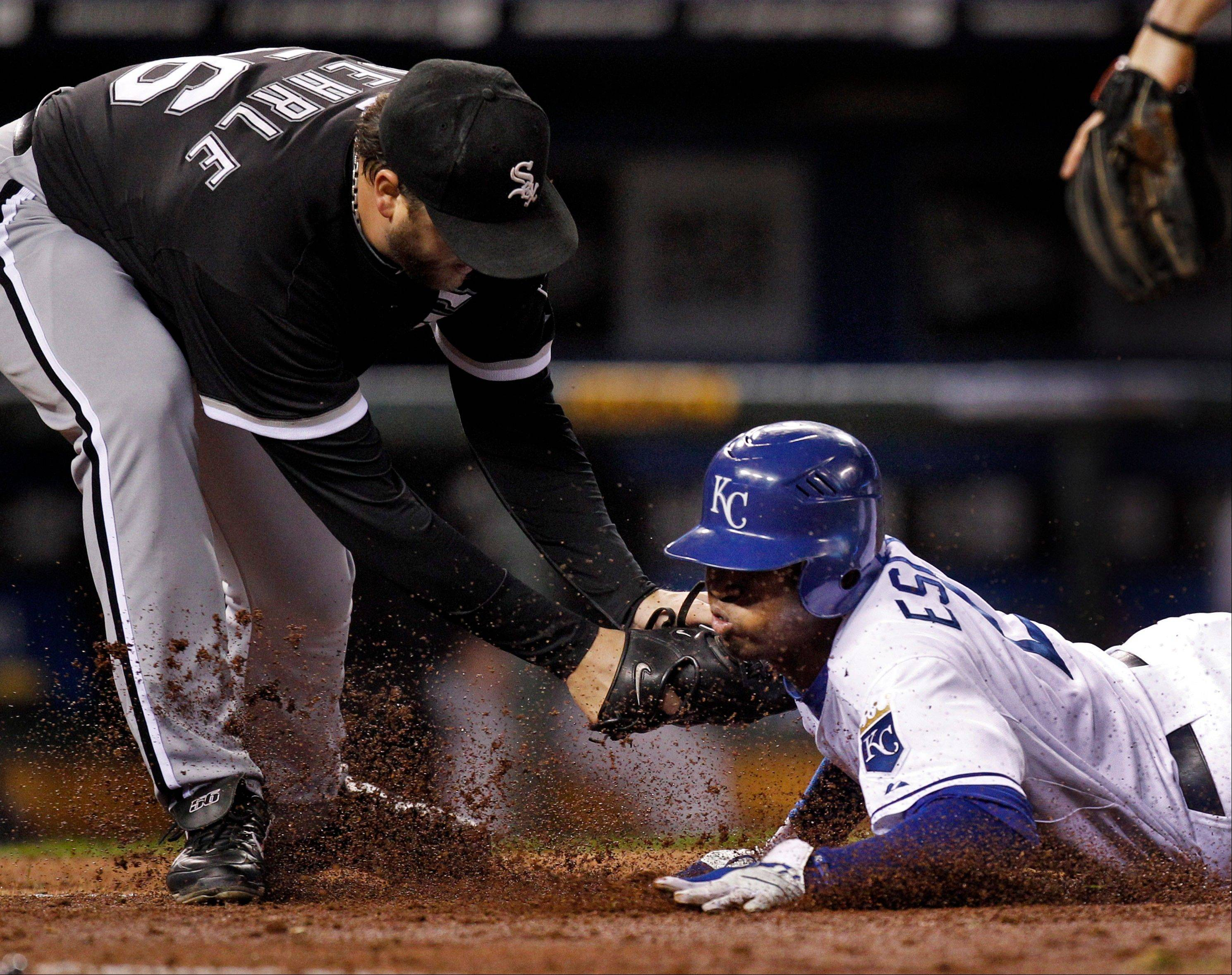 The Royals' Alcides Escobar is tagged by Chicago White Sox starting pitcher Mark Buehrle Thursday during the fourth inning.