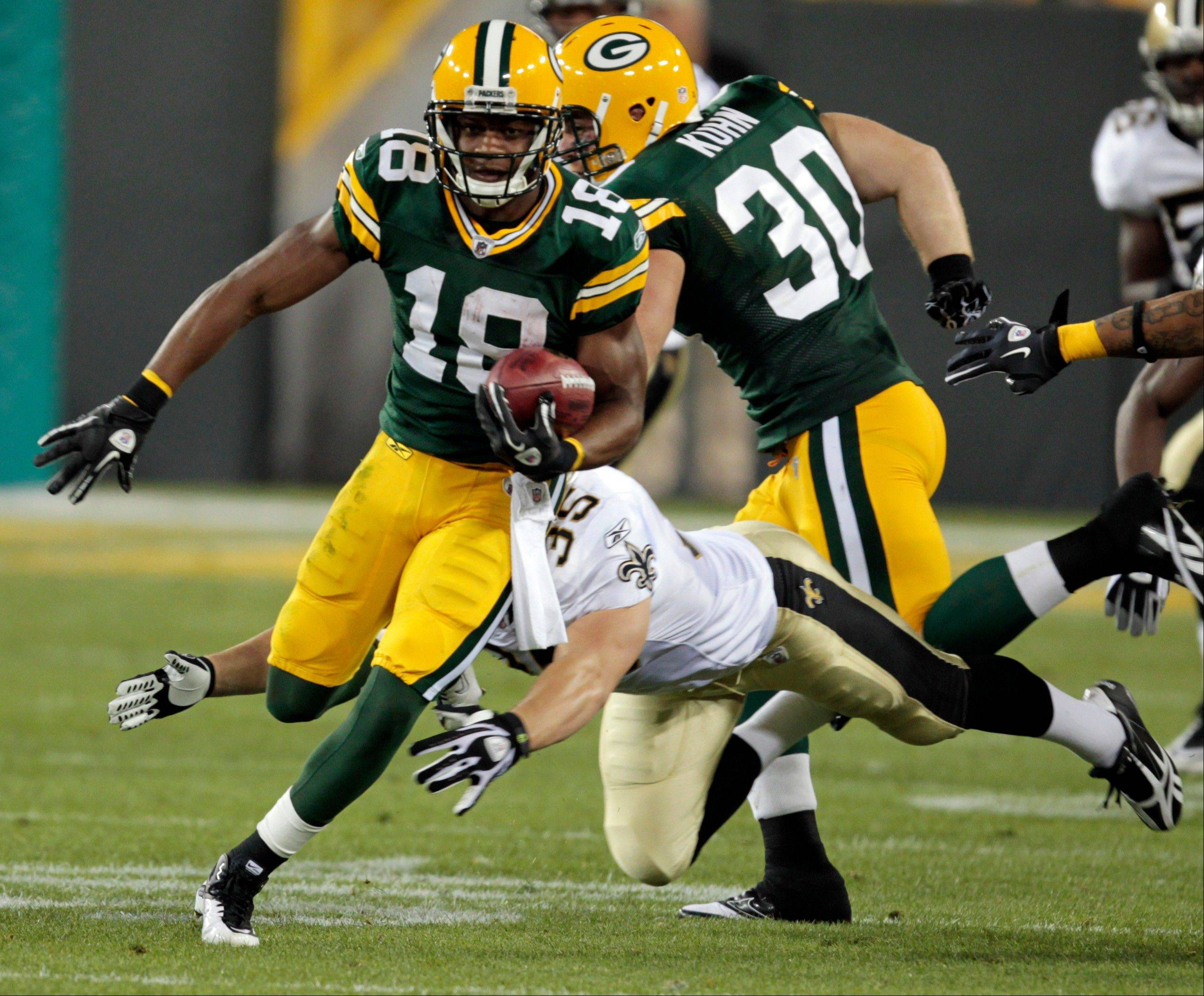 The Green Bay Packers' Randall Cobb gets past New Orleans Saints' Korey Hall during his 108-yard kickoff return