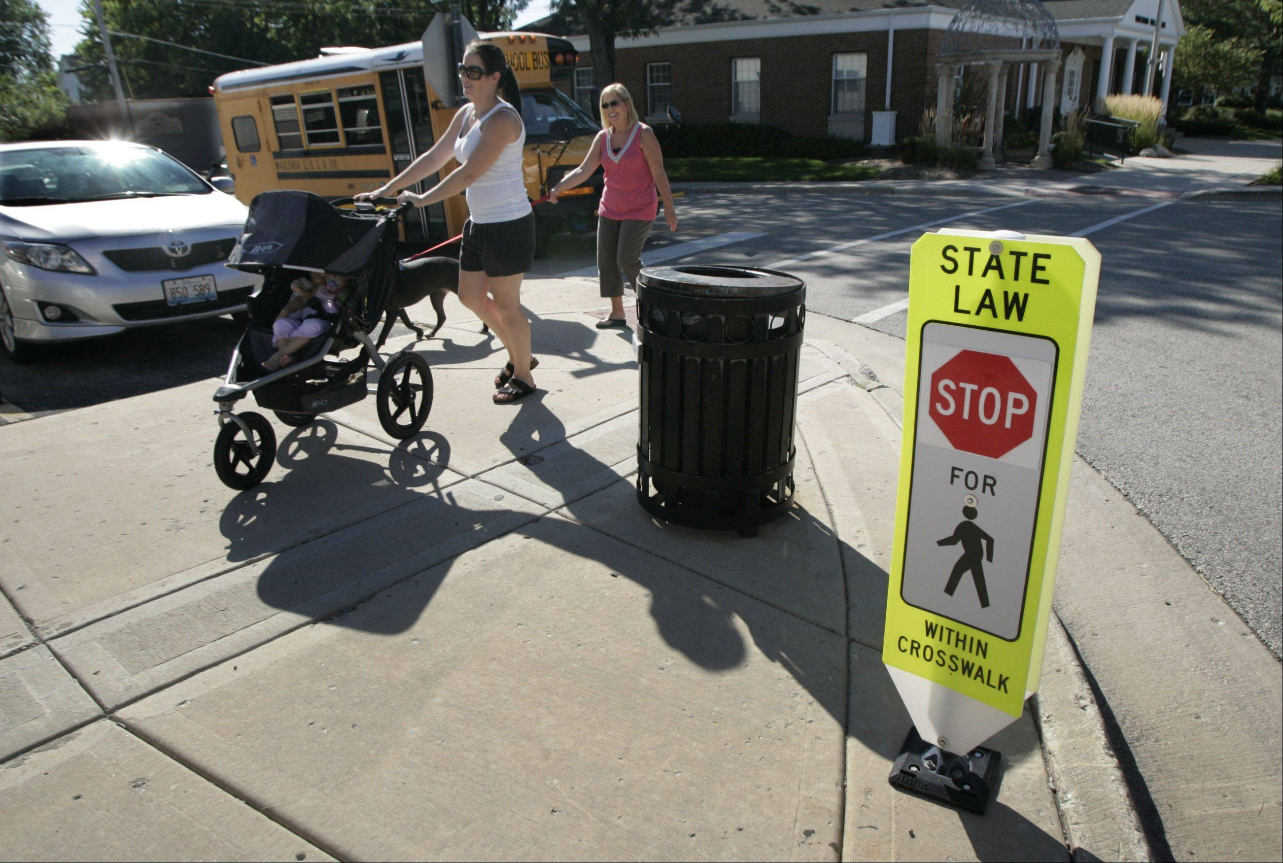 Jodi Romans and her 18-month-old daughter, Lonni, and friend Linda Wagner with her dog, Riley, use a crosswalk on Main Street in downtown Wauconda. Illinois beefed up its crosswalk law in July 2010.