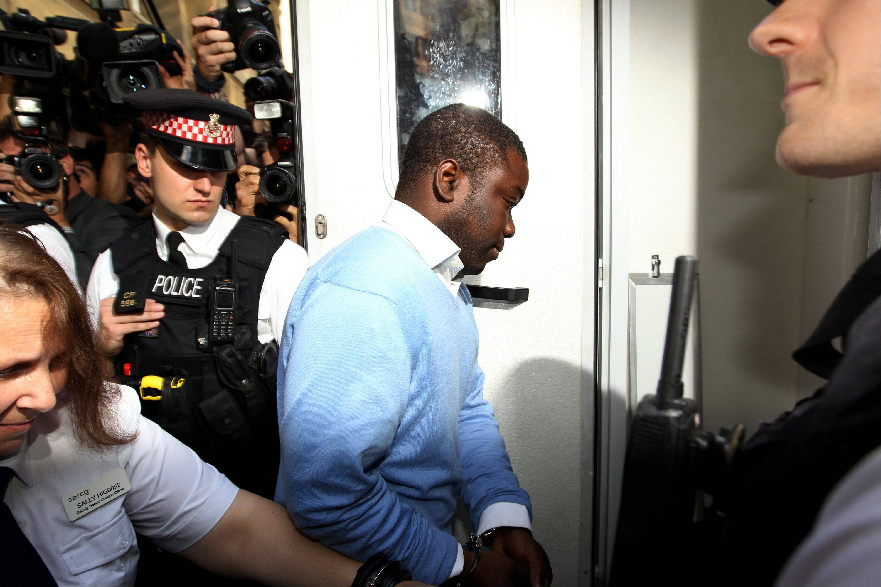 Kweku Adoboli, the UBS trader, center, enters a prison van following his appearance at the City of London magistrates court in London, U.K., on Friday. Adoboli, the trader arrested on suspicion of fraud at UBS AG, hired lawyers at Kingsley Napley LLP in London to represent him, a spokeswoman for the law firm said today in a phone interview.