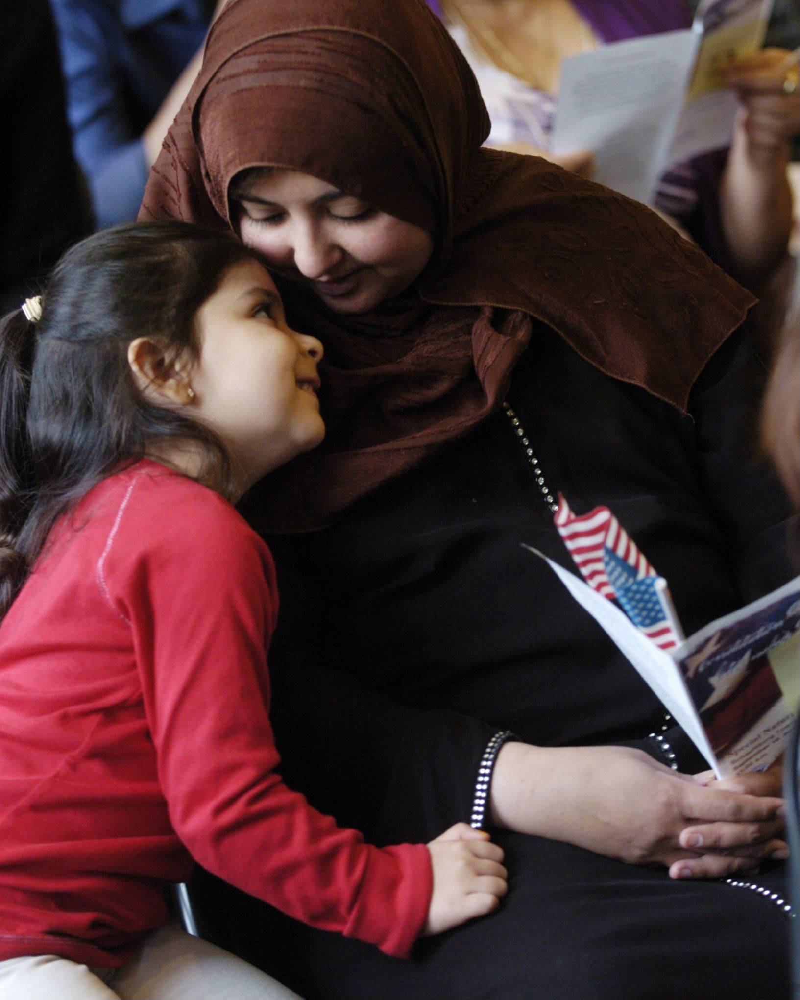 Shabniz Musani of Bolingbrook sits with her daughter, Saadia, 3, before taking the oath of citizenship during a naturalization ceremony Friday at the Schaumburg Township District Library.