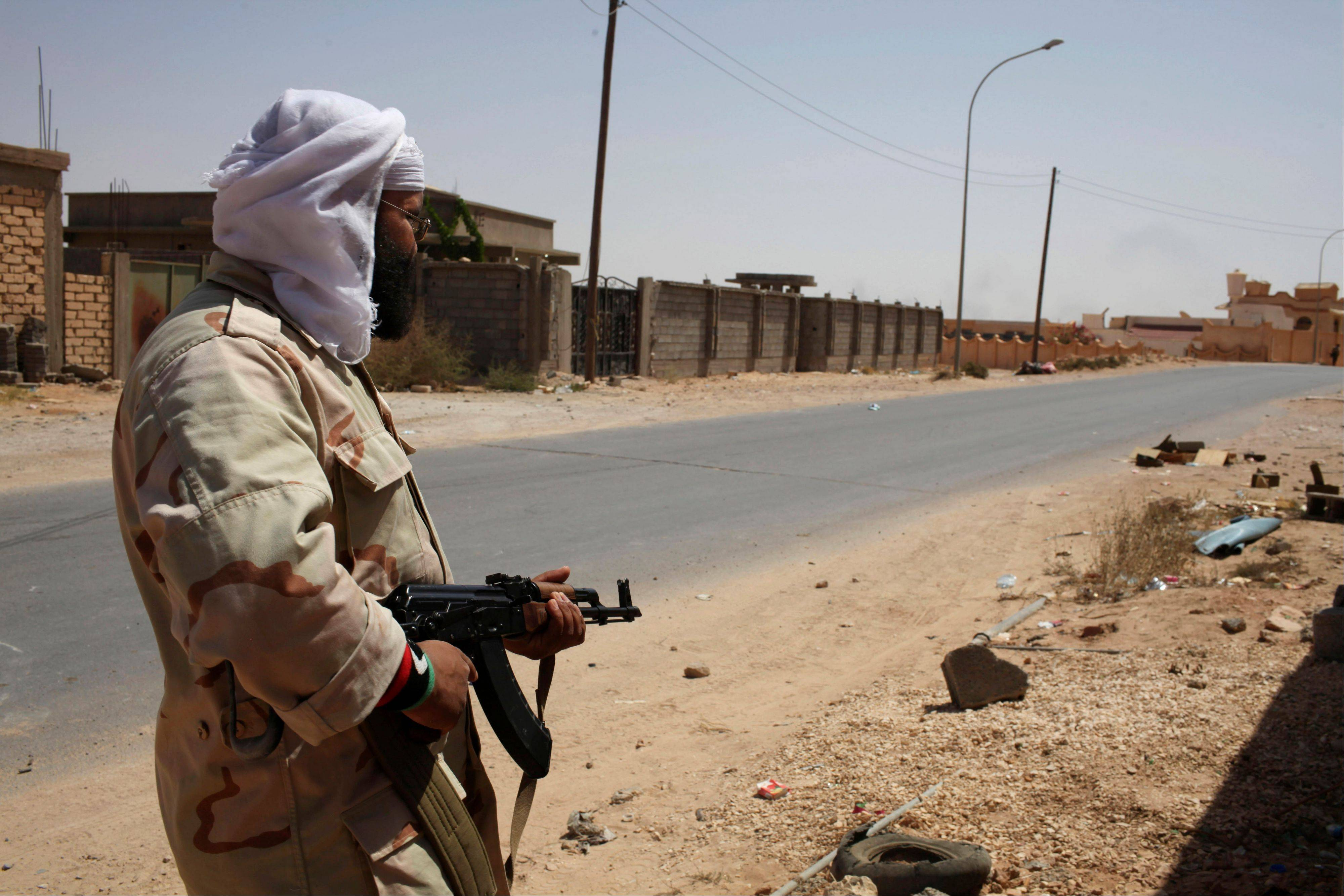 A Libyan fighter guards a road in Bani Walid, Libya, Friday.