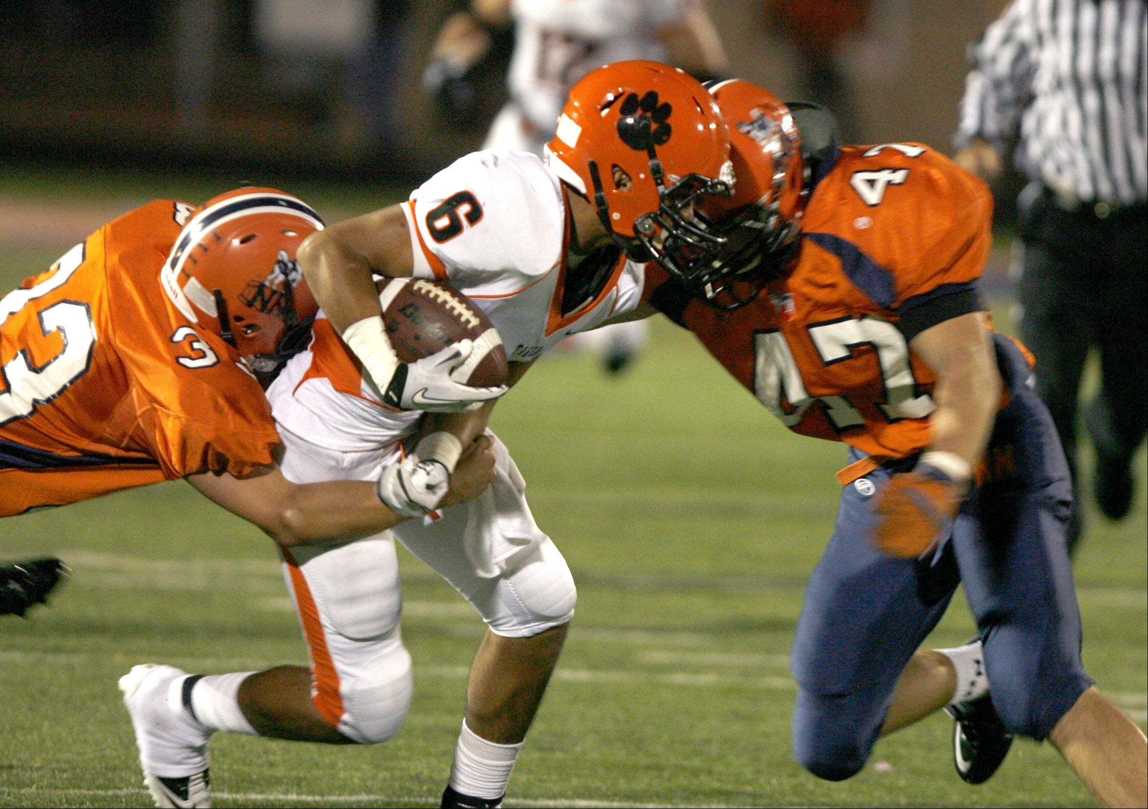 Naperville North High School's Kevin Walsh (33) and Tim Davis (47) tackle Wheaton Warrenville South High School's Brady Banda (6).
