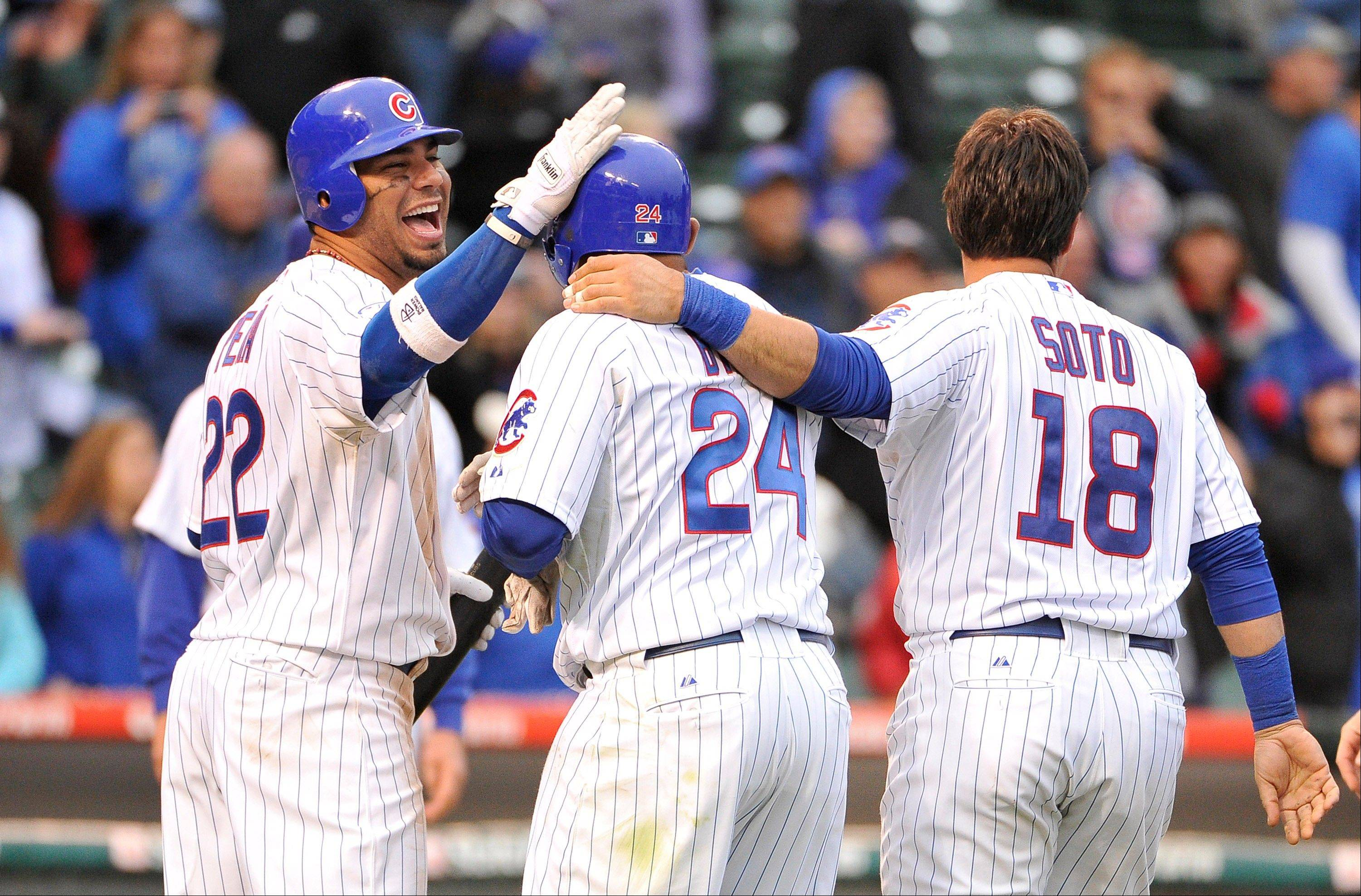The Cubs' Carlos Pena, left, and Geovany Soto congratulate Marlon Byrd after Byrd hit a game-winning RBI-single that scored Starlin Castro for a 4-3 victory in the 12th inning Friday against the Astros at Wrigley Field.