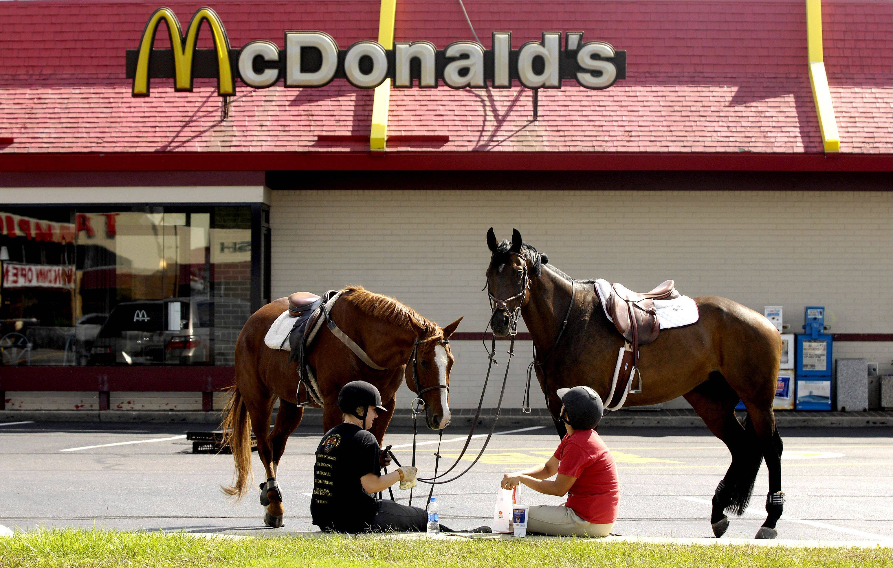 Shelby Watts of Wayne, left, with her horse, Calvin, and Alexis Muuss of Bartlett, accompanied by Ivy, take a break at the West Chicago McDonald's on Route 59.