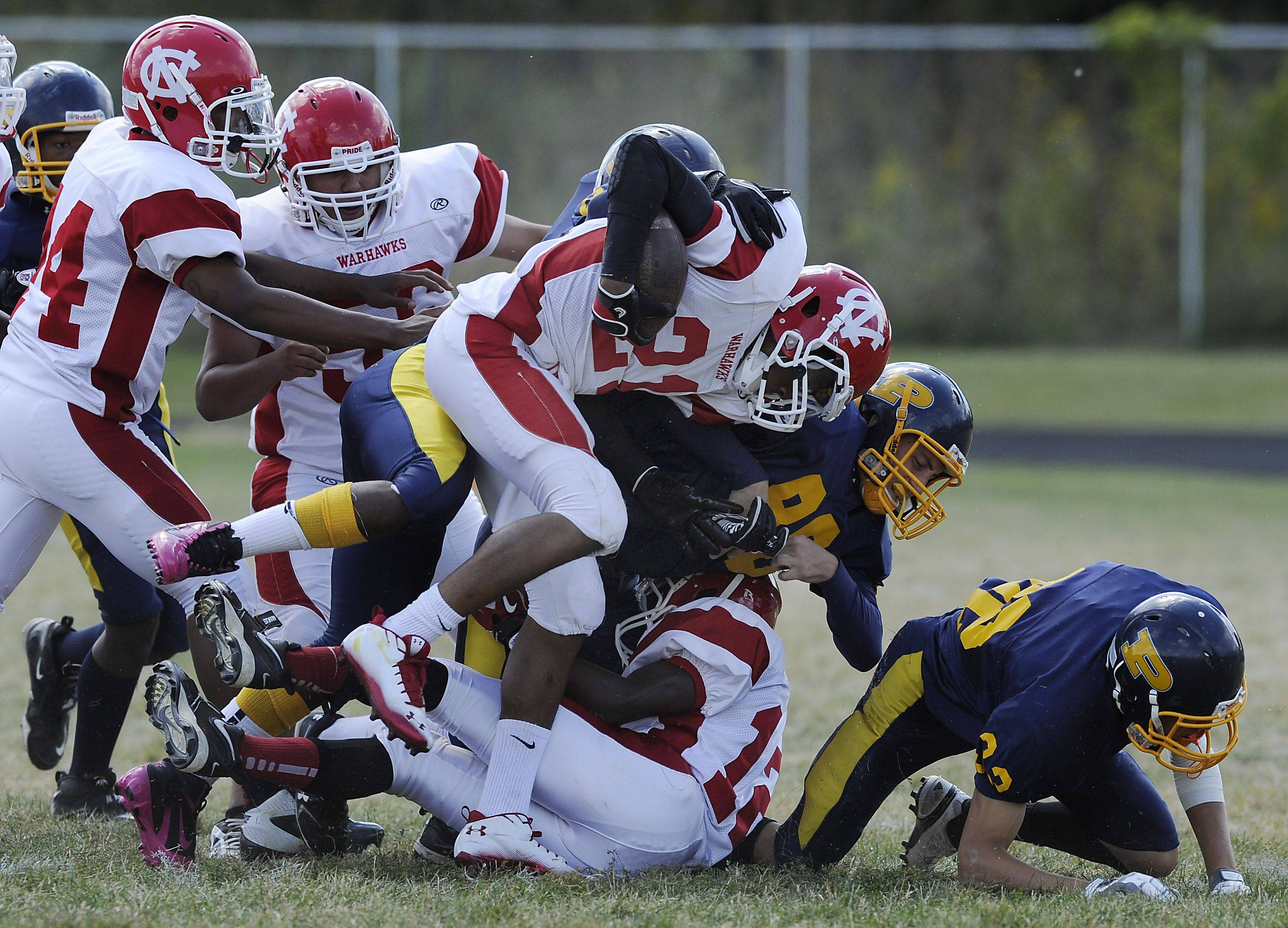 North Chicago's Manros Nickens plows over Round Lake's defense in the first quarter for major yardage in their matchup on Saturday at Round Lake High School.