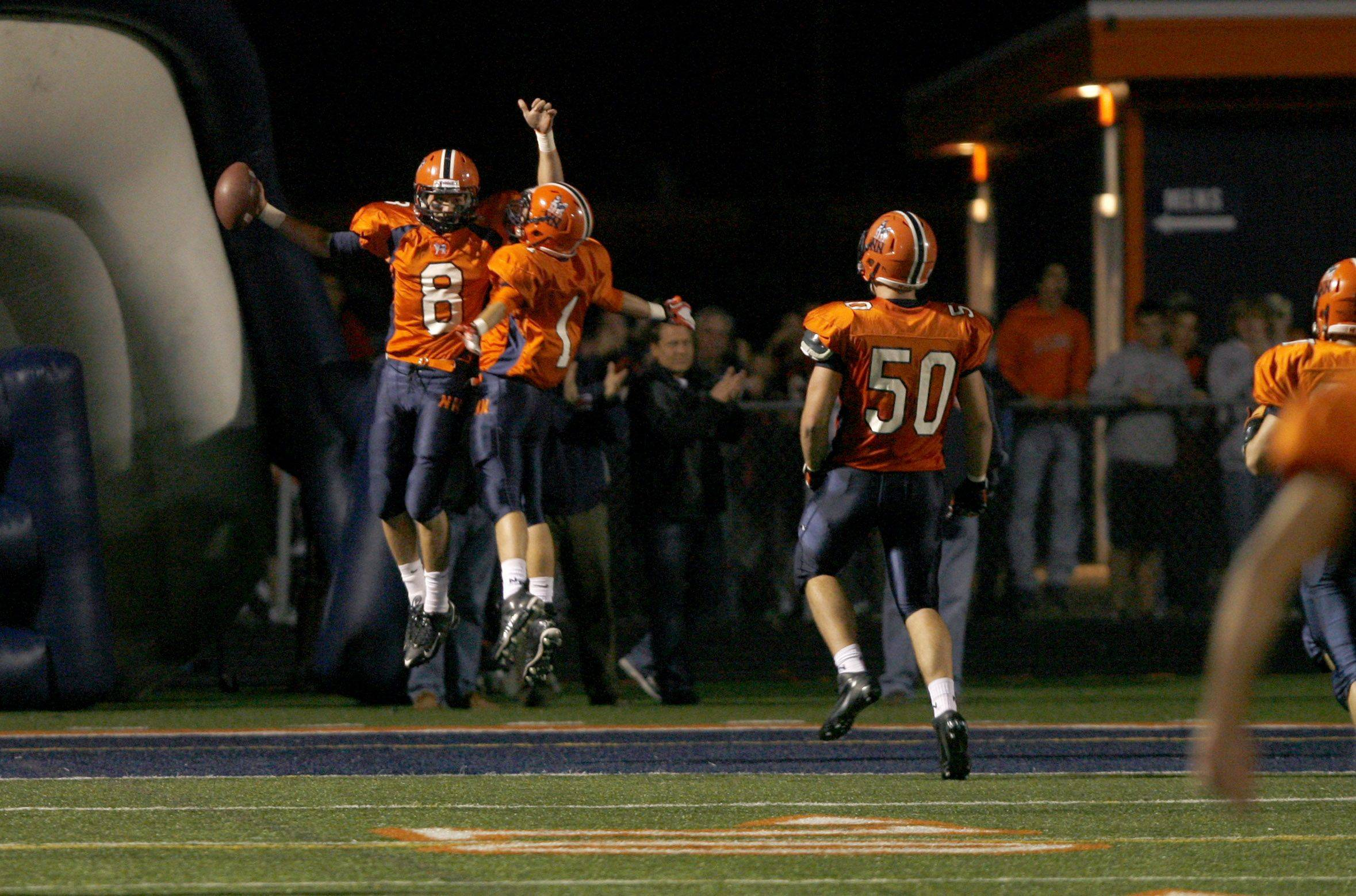 Week 4- Naperville North High School's Tyler Gehr celebrates a first-half touchdown run with Tim LaScala. Mike Langman watches the play.