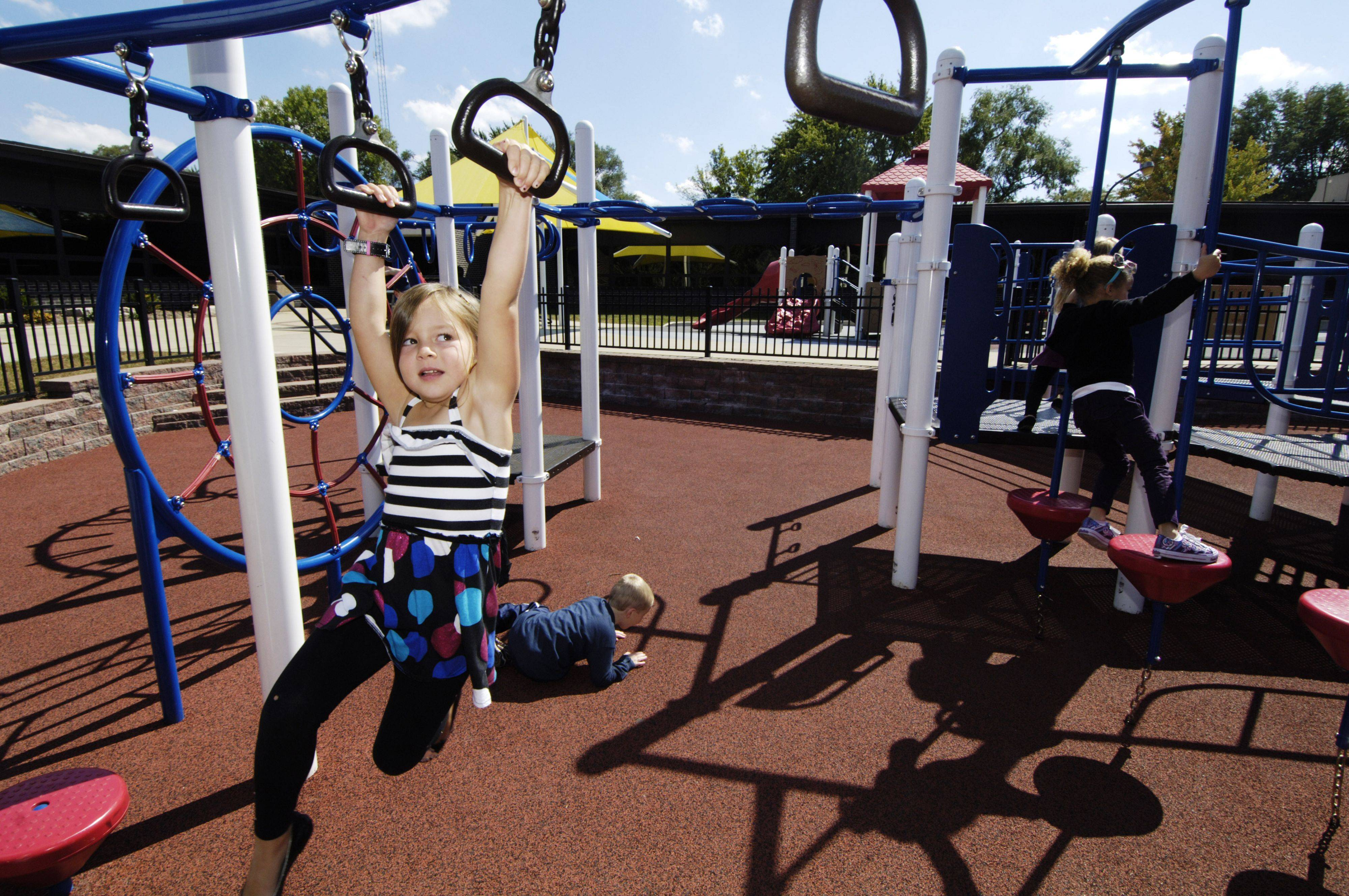 Cami Kazian, 6, of Libertyville plays on the new Alcott Park playground before its dedication Saturday in Buffalo Grove. The adjacent playground was dedicated to the memory of her sister, Lexi.