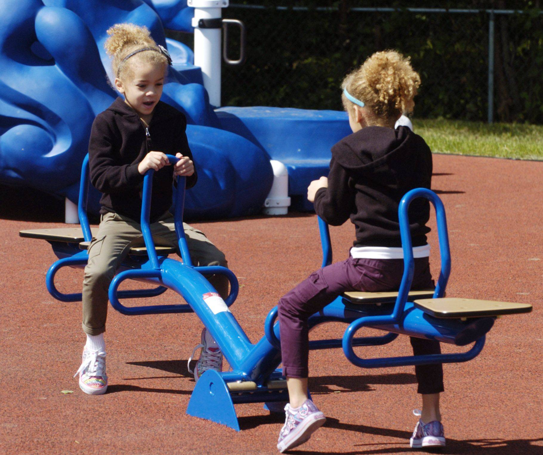 Twins Madeline, left, and Olivia Lawhorn, 5, of Vernon Hills play on the playground dedicated to the memory of Lexi Kazian at Alcott Park in Buffalo Grove Saturday.
