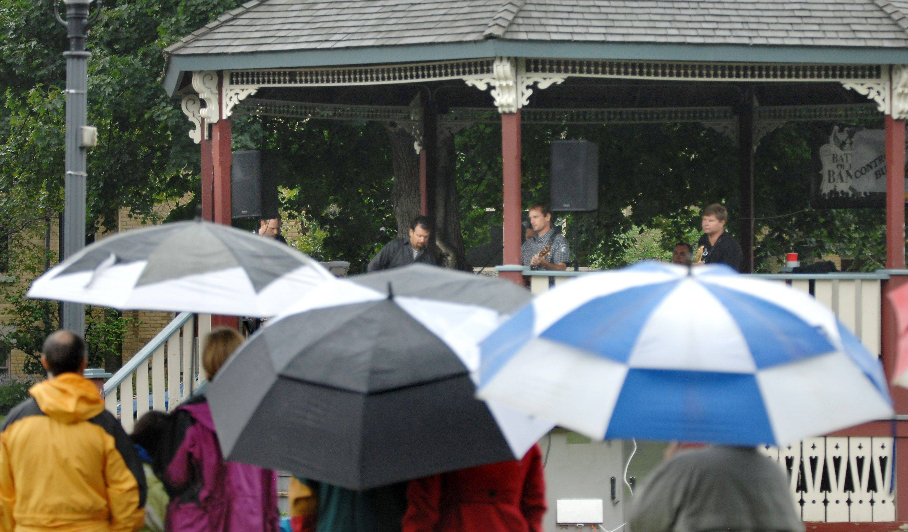 Umbrellas fill Grafelman Park as local bands play on the pavilion during a rainy Heritage Festival Sunday in West Dundee. The weather canceled the parade, but the festival remained open.