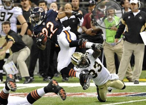 Bears running back Matt Forte (22) is tripped by New Orleans Saints cornerback Jabari Greer (33) during the first quarter.
