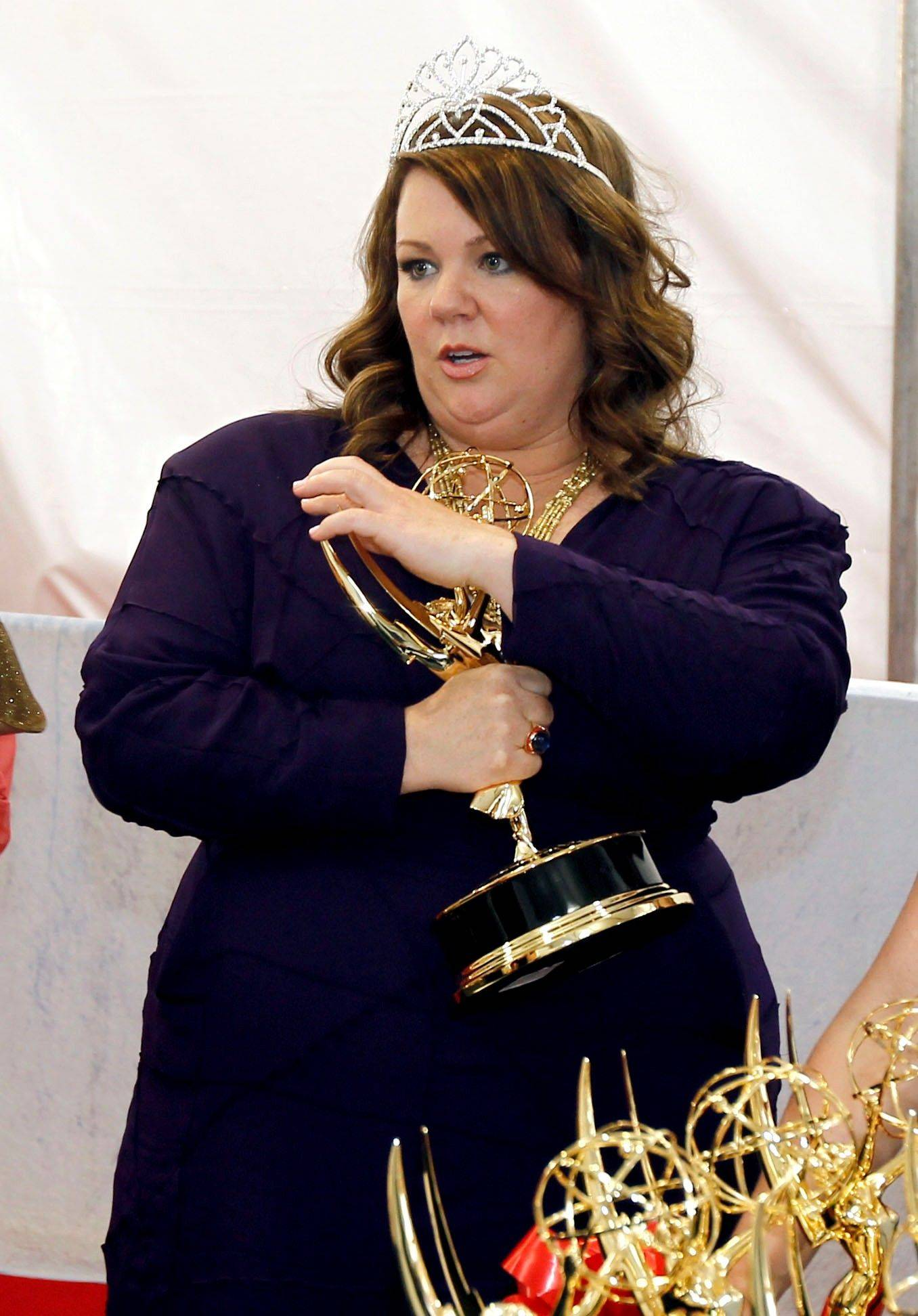 Melissa McCarthy keeps her Emmy for outstanding lead actress in a comedy series close to her while she hangs out backstage.