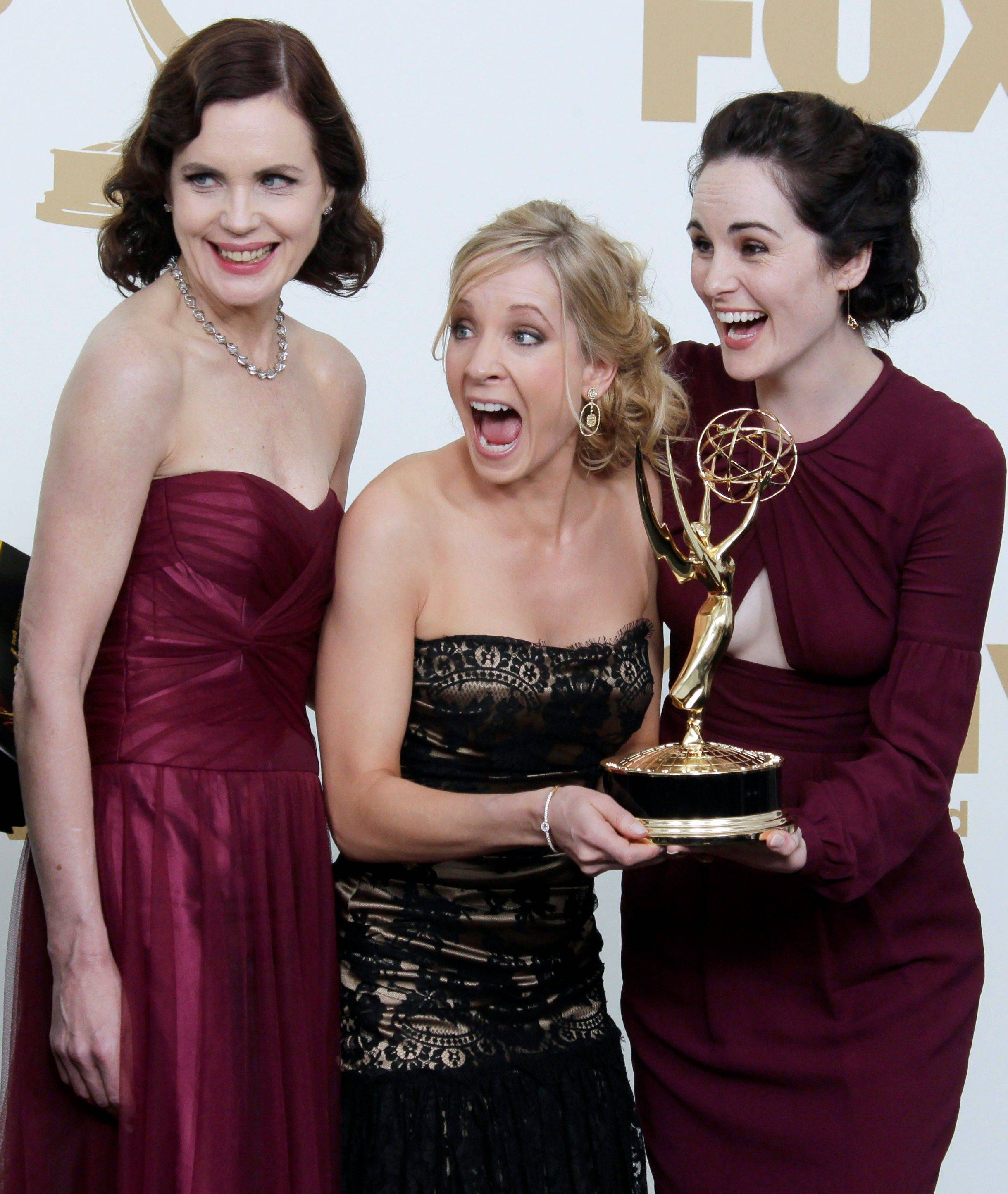 """Downton Abbey"" cast members from left, Elizabeth McGovern, Joanne Froggatt and Michelle Dockery pose for a photograph backstage. ""Downton Abbey"" won for outstanding writing and outstanding miniseries or movie."