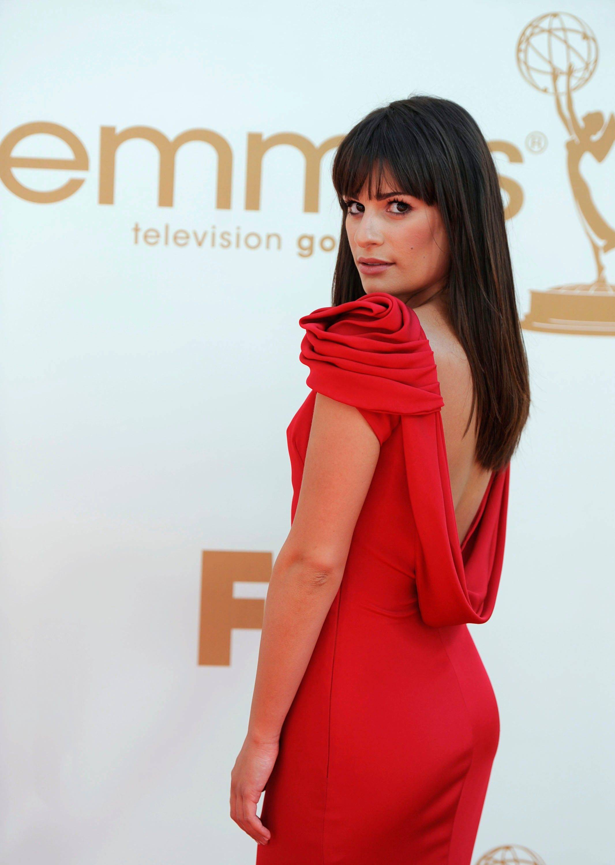 """Glee"" star Lea Michele, in an elegant Marchesa gown, elicits whoops and cheers from the crowd in the bleachers as she makes her way down the red carpet."