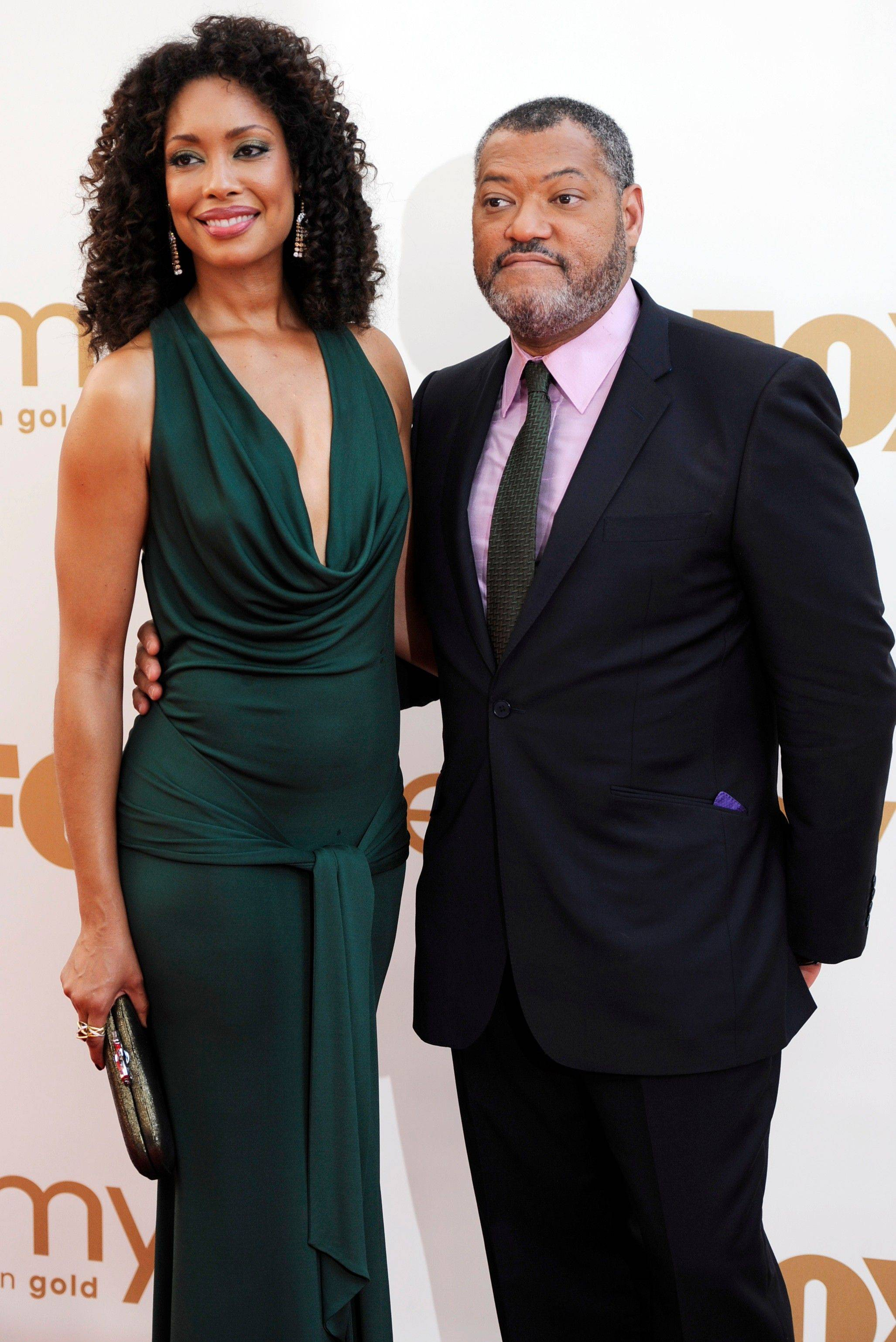 Actress Gina Torres and actor Laurence Fishburne keep each other close on the red carpet.