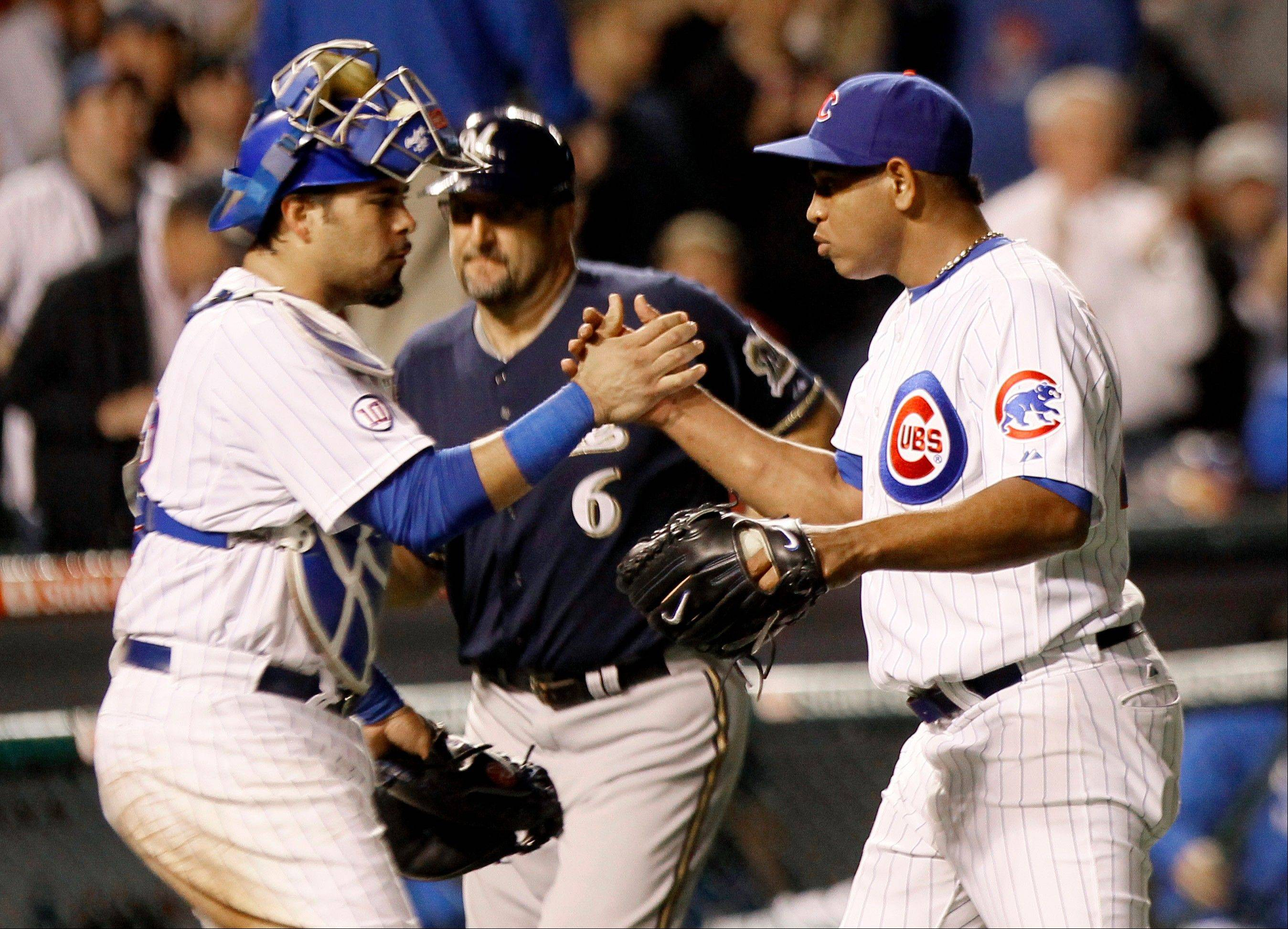 Chicago Cubs catcher Geovany Soto, left, celebrates with teammate relief pitcher Carlos Marmol, the Cubs� 5-2 win over the Milwaukee Brewers, as Brewers third base coach Ed Sedar heads back to the dugout after a baseball game Monday, Sept. 19, 2011, in Chicago.