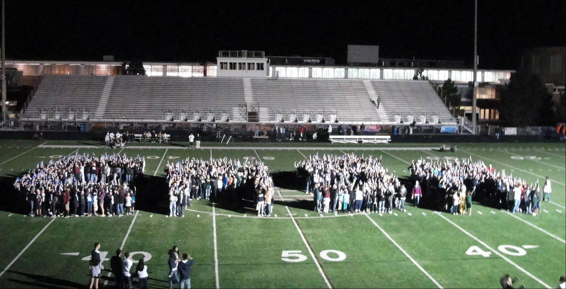 "The 826 people who formed the letters ""CASA"" on the Stevenson High School football field Saturday evening in an attempt to set the world record for largest glow stick design."
