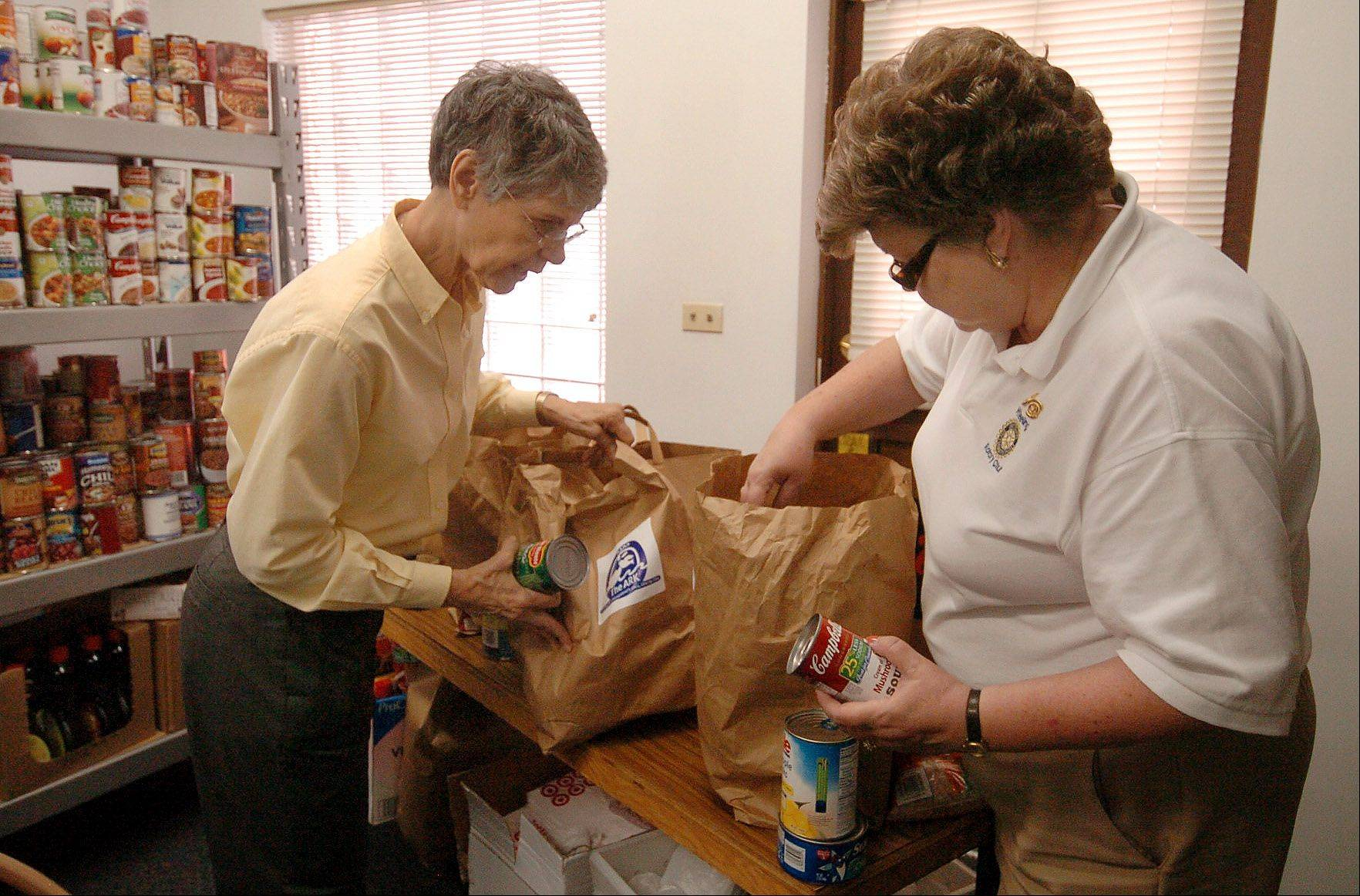 Barbara Bradley, left, and Karen Pradun sort through groceries.