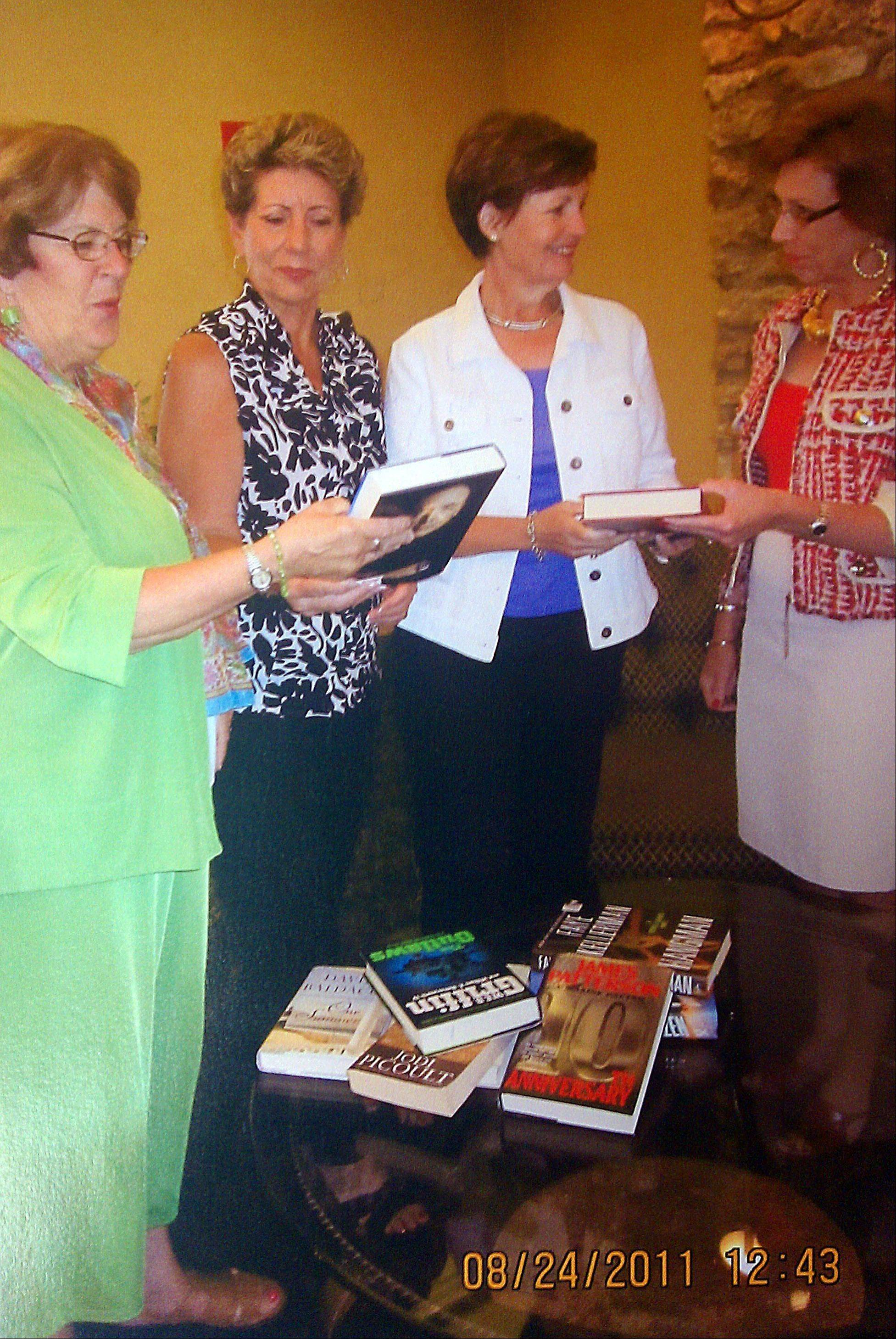 Elgin Donor Club members Mary Aydt, Charlene Devine, Claire Johannesen and Merrie Derderian look over the gently used books that will be for sale during the annual Book Review and Tea Sept. 29.