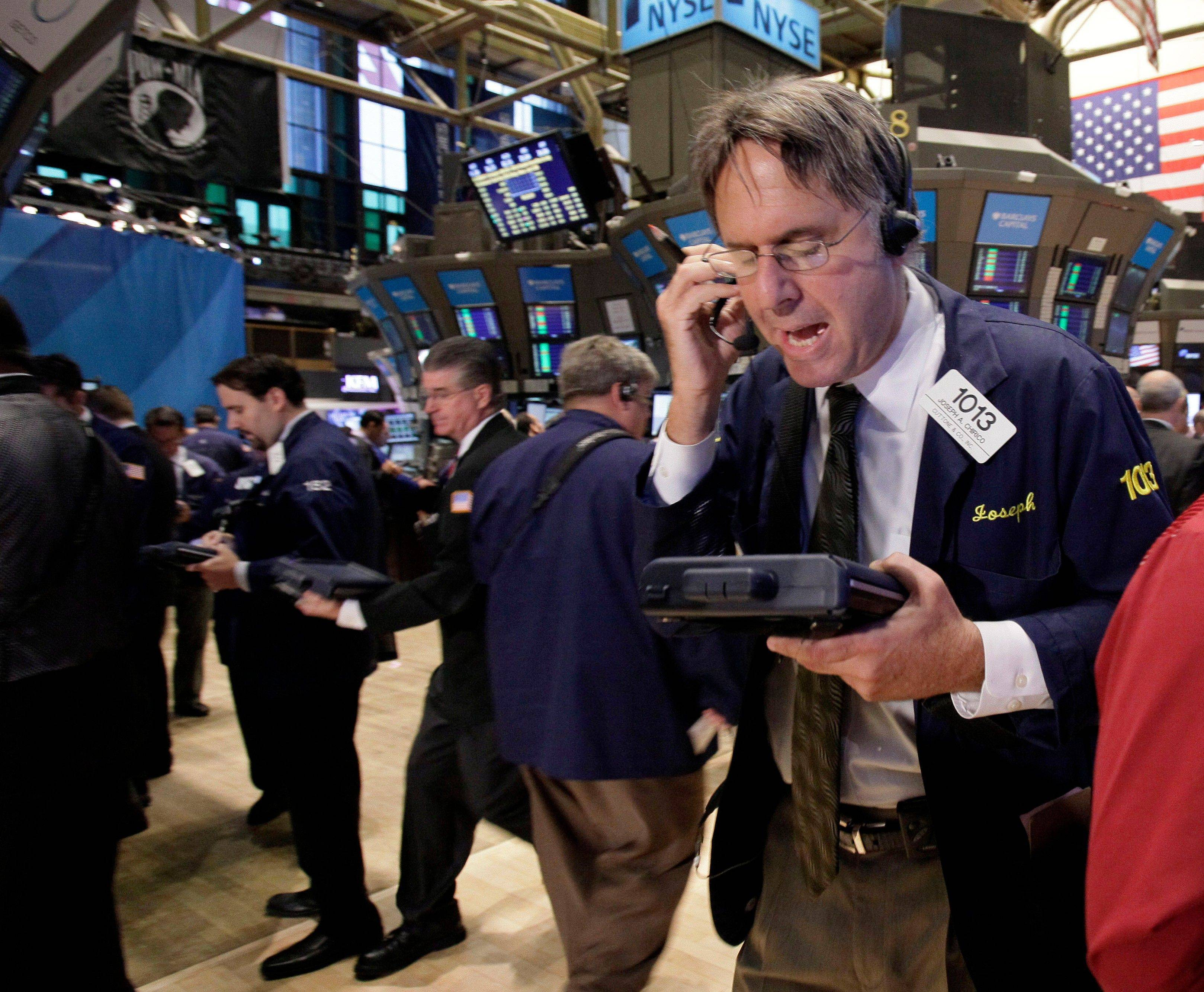 Trader Joseph Chirico works on the floor of the New York Stock Exchange. Global stocks brushed aside the latest credit rating downgrade of Italy as investors hoped Greece would make progress in discussions with debt inspectors to get its hands on more bailout money Tuesday.