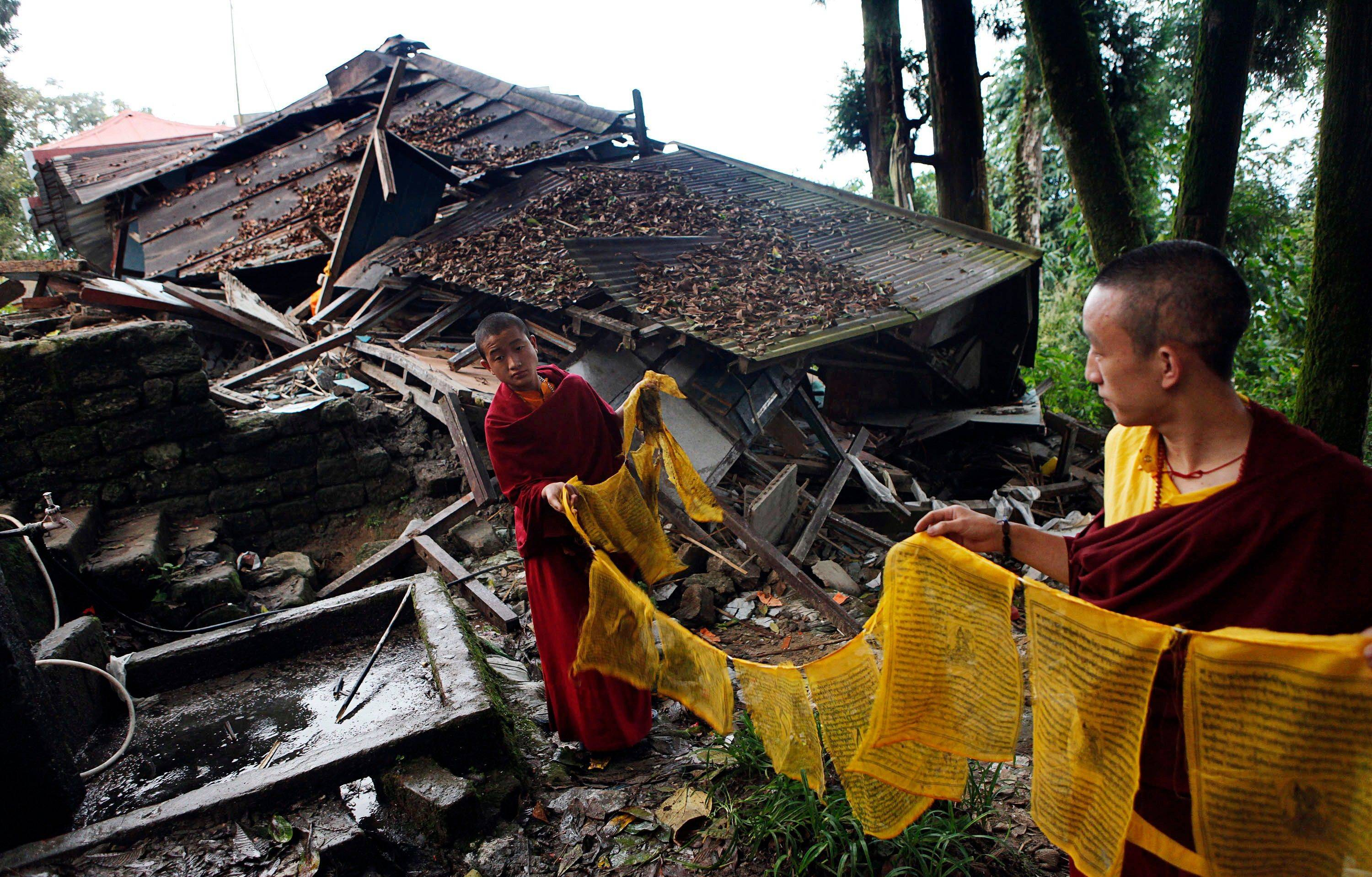 Buddhist monks hold the spiritual flags Tuesday near the rubble at Enchey Monastery, India. Thousands of terrified survivors of a Himalayan earthquake that killed many people and shook parts of India, Nepal and China crowded Tuesday into shelters and relatives� homes or stayed out in the open for fear of aftershocks.