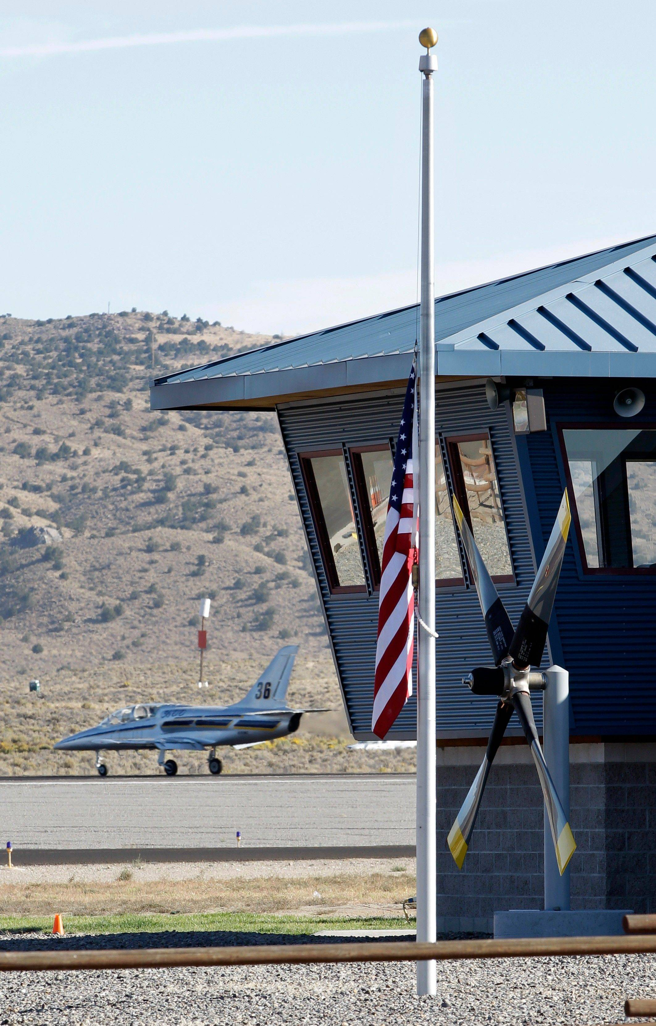 A plane prepares to take off Monday as an American flag flies at half-staff in front of a control tower at an airport in Reno, Nev., where the Reno Air Races were held.