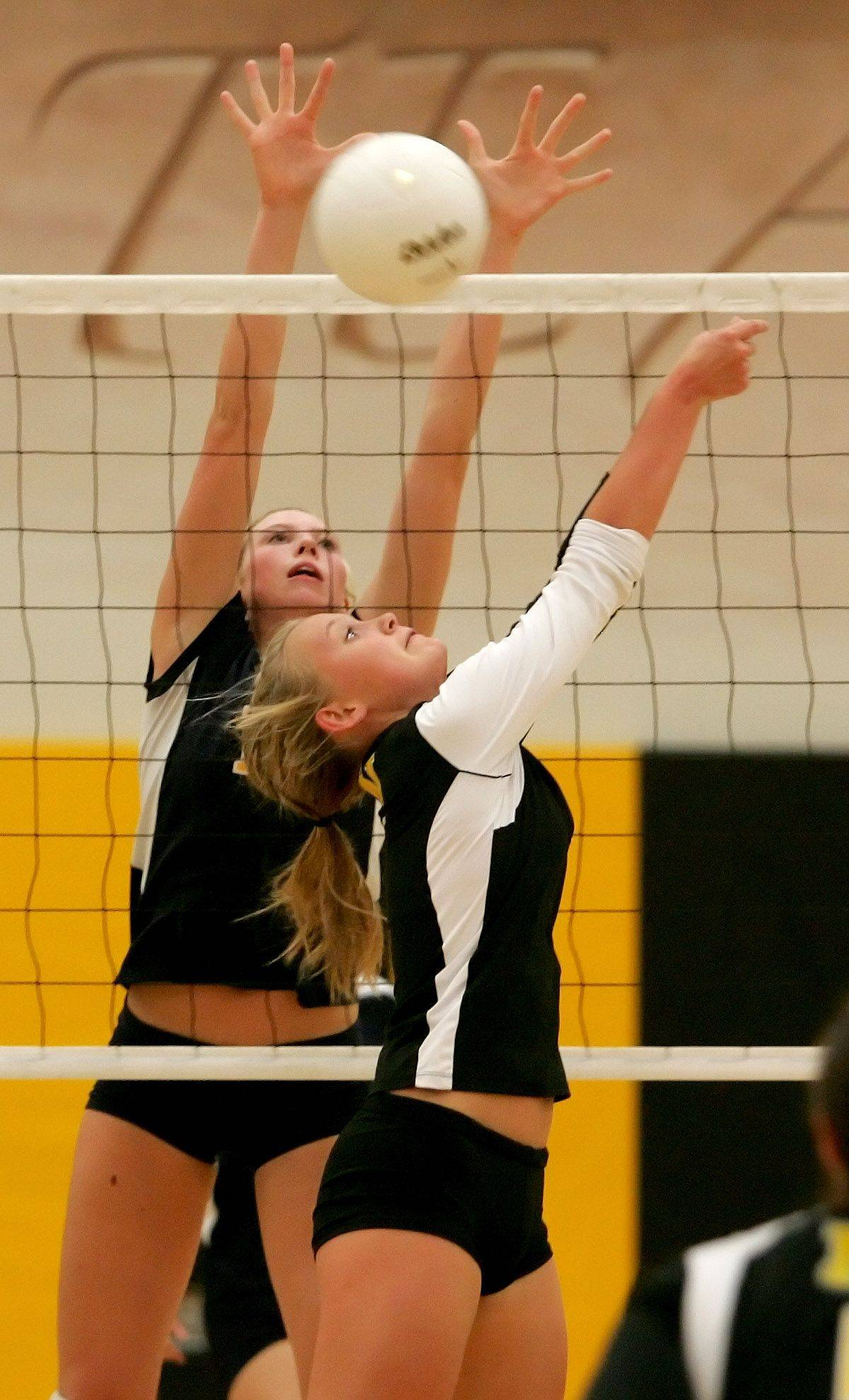 Callie Huebener of Neuqua Valley goes up to block a shot by Ellie Petersen of Metea Valley during girls volleyball Tuesday in Aurora.