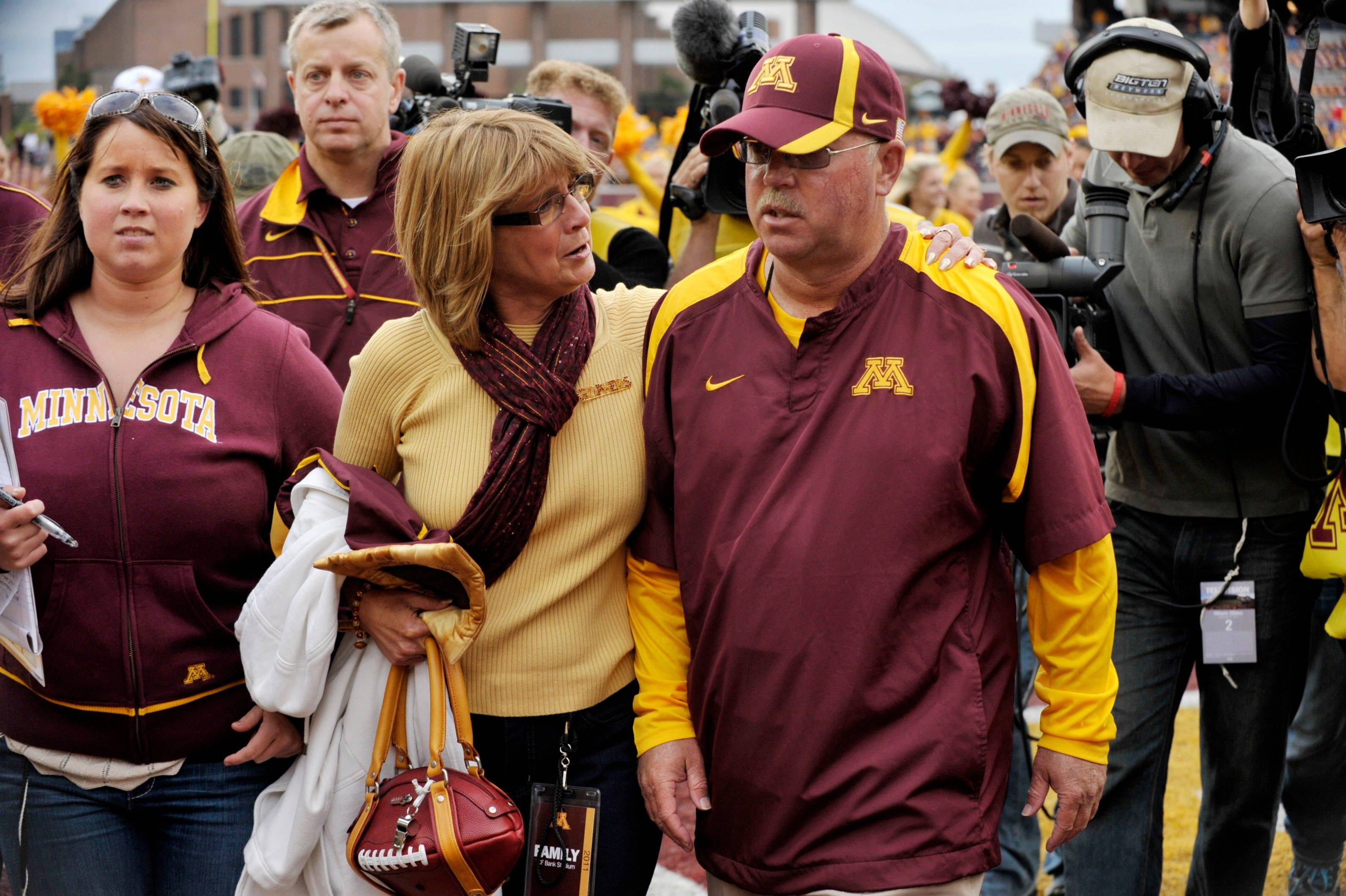 Minnesota coach Jerry Kill, front right, leaves the field with his wife, Rebecca after Minnesota defeated Miami, Ohio, 29-23 for Kill's first win at Minnesota in an NCAA football game on Saturday, Sept. 17, 2011, in Minneapolis. (AP Photo/Tom Olmscheid)