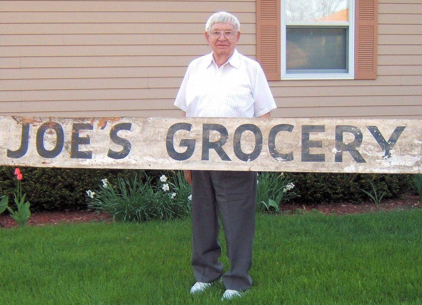 "Roland ""Joe"" Josephson holds the sign from the grocery store he operated in the 1960s. The sign was located by his daughter, Rita, while visiting her childhood home and donated to the family by the present homeowners."