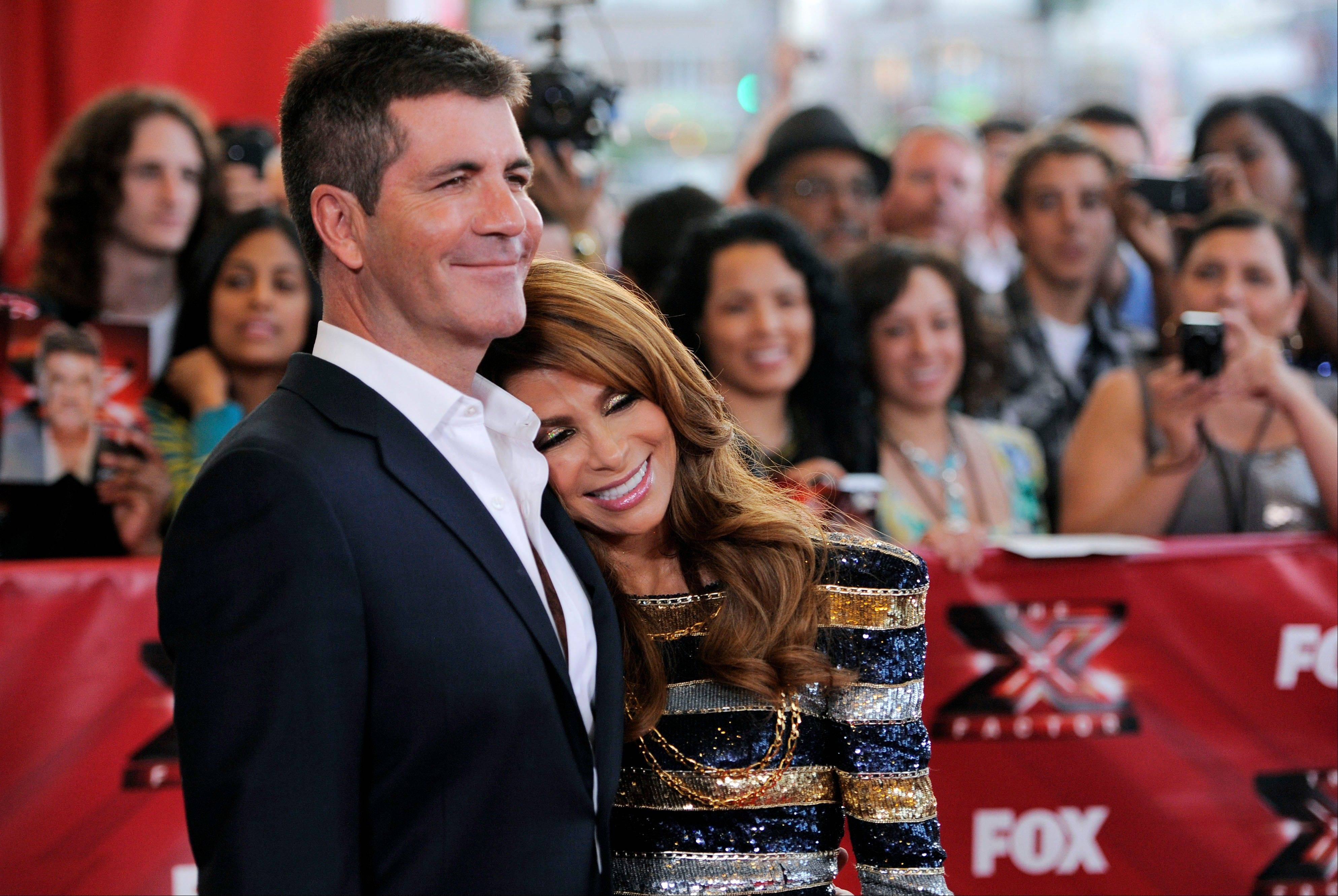 "Simon Cowell, left, and Paula Abdul, judges on ""The X Factor"" pose together at a world premiere screening event for the new television series."