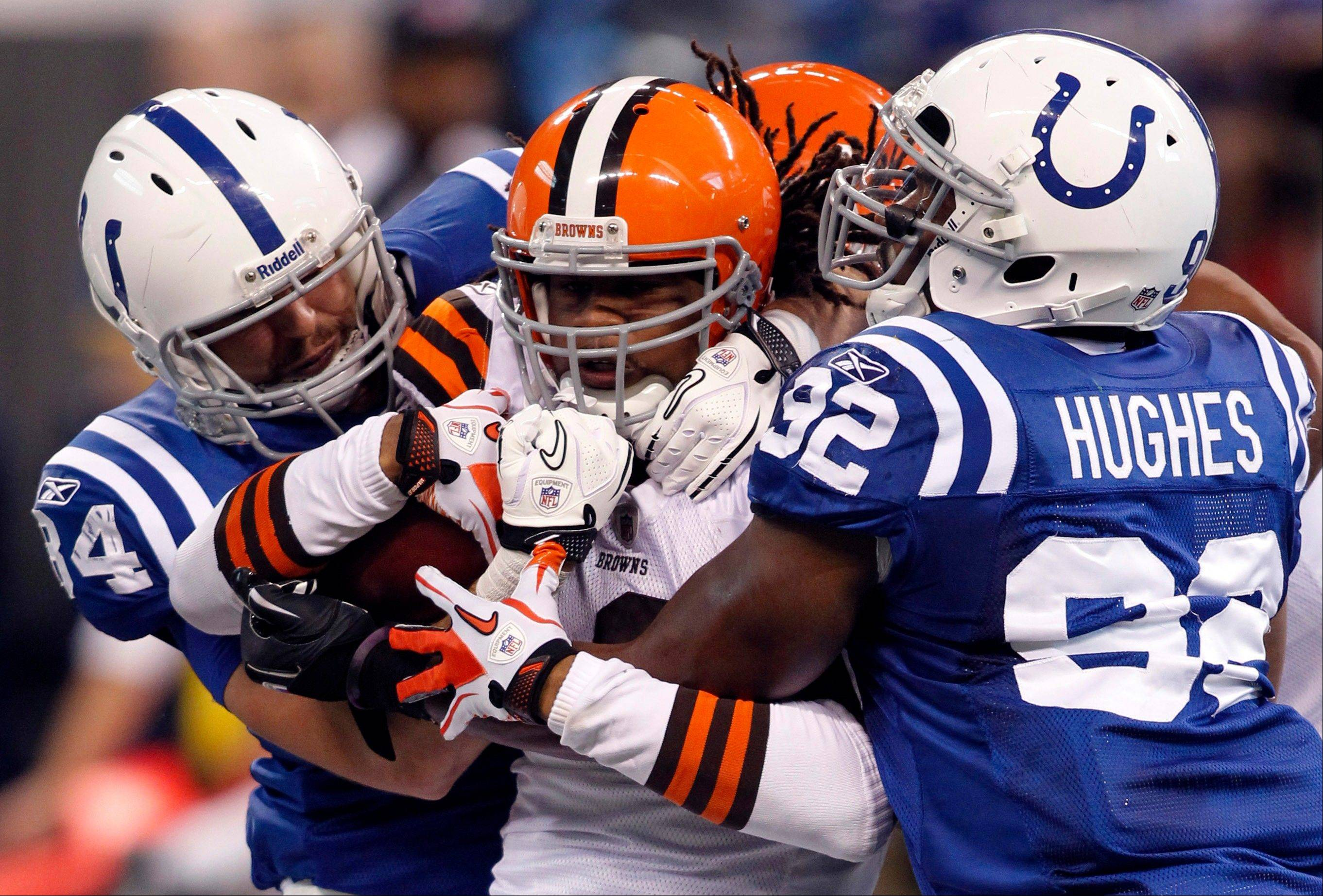Cleveland Browns wide receiver Josh Cribbs, center, is tackled by Indianapolis Colts� Jerry Hughes, right, and Jacob Tamme on a kickoff-return in the third quarter Sunday.