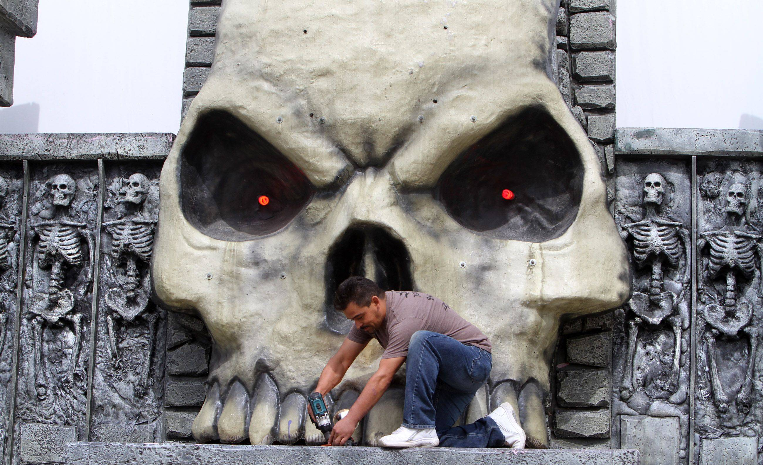Crew Chief Tello Wilfrido Thursday installs a plate cover over a light at the entrance to Scream in the Park in Rosemont's entertainment district.