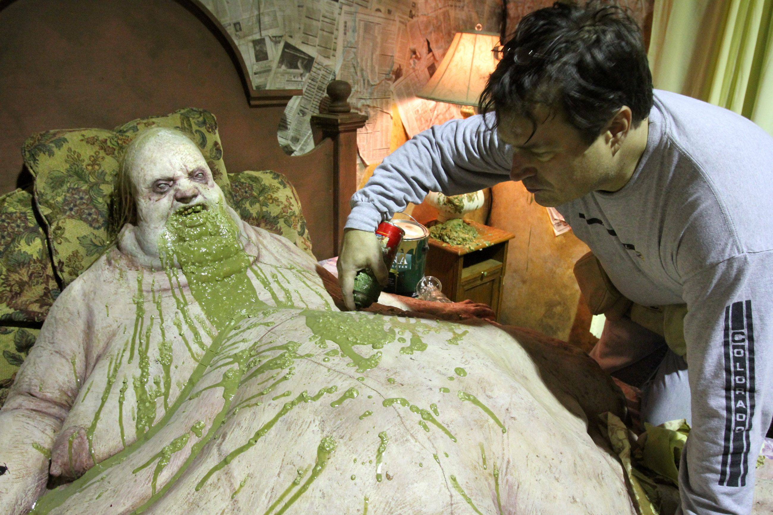 Master designer Mark Kaschube, who is also a dentist in Franklin Park, sprays paint on a prop mannequin that will be on display at Scream in the Park in Rosemont's entertainment district.