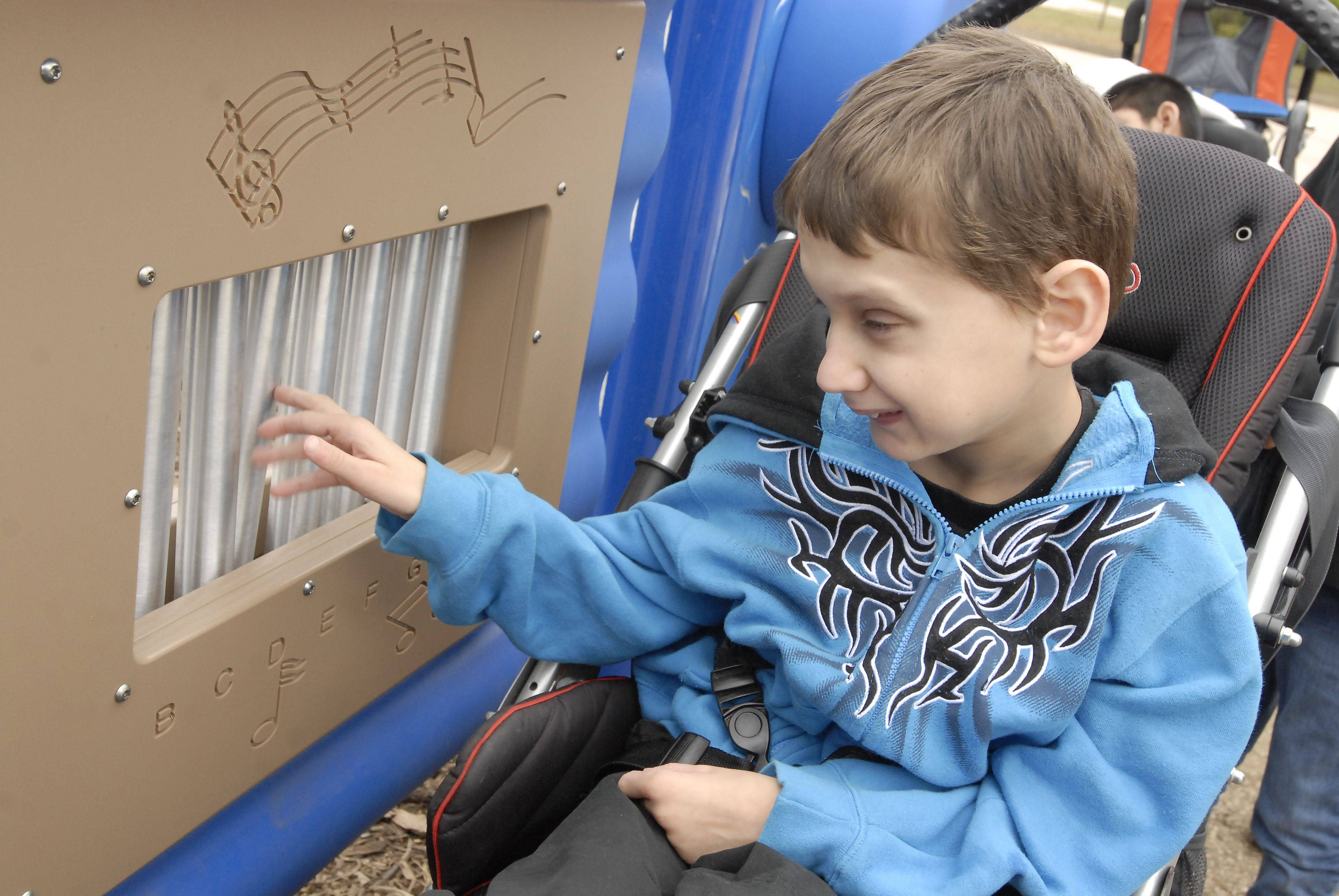 Hunter Smith plays the chimes on a panel for disabled children at the new playground at Nature Ridge Elementary School in Bartlett. They would like to raise more funds for additional panels.