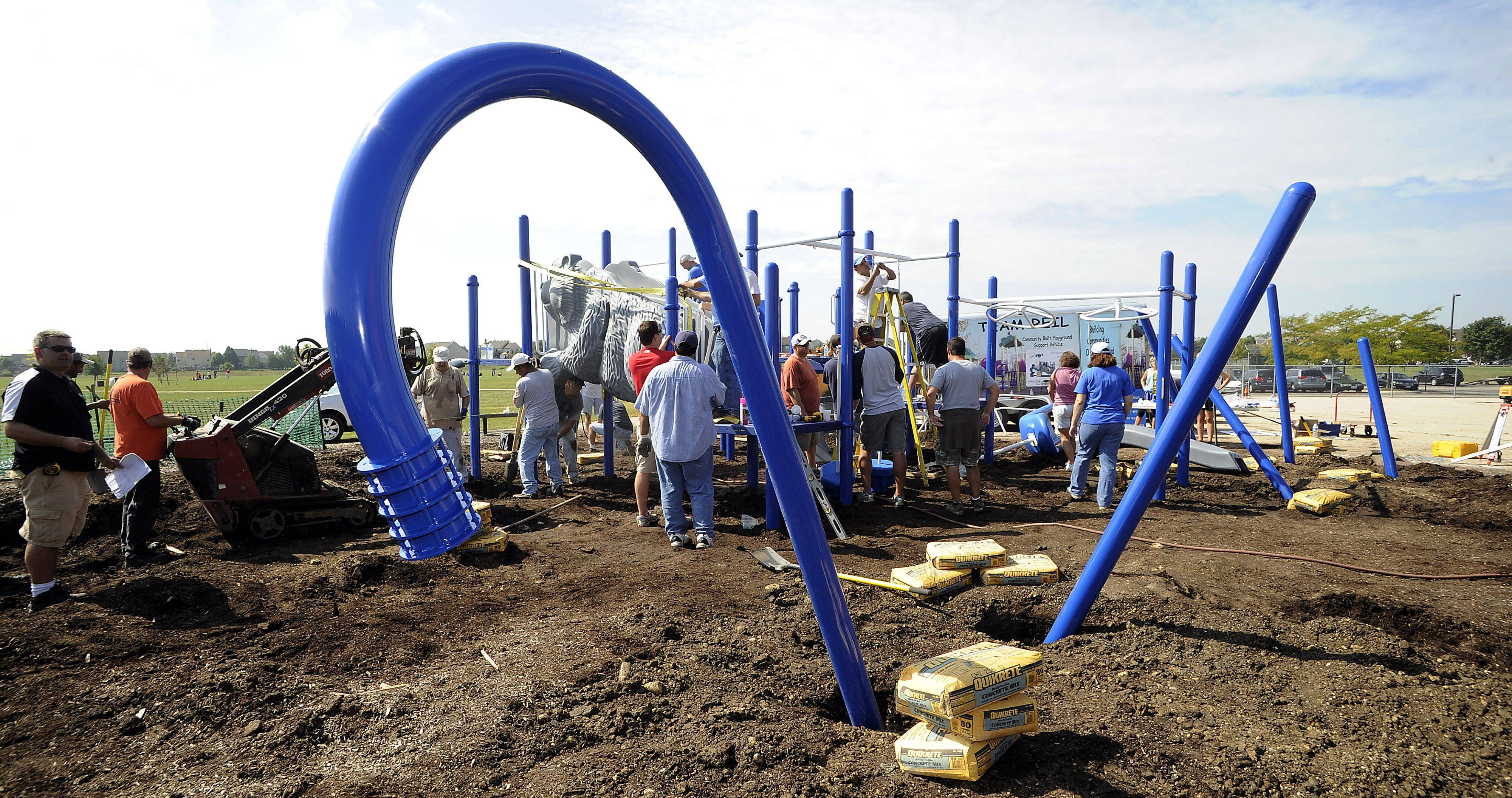 Poles of the playground set look like giant candy canes as parents of Nature Ridge Elementary School in Bartlett begin to build a new playground recently that was PTO-funded for all the kids in the school, including students with disabilities.
