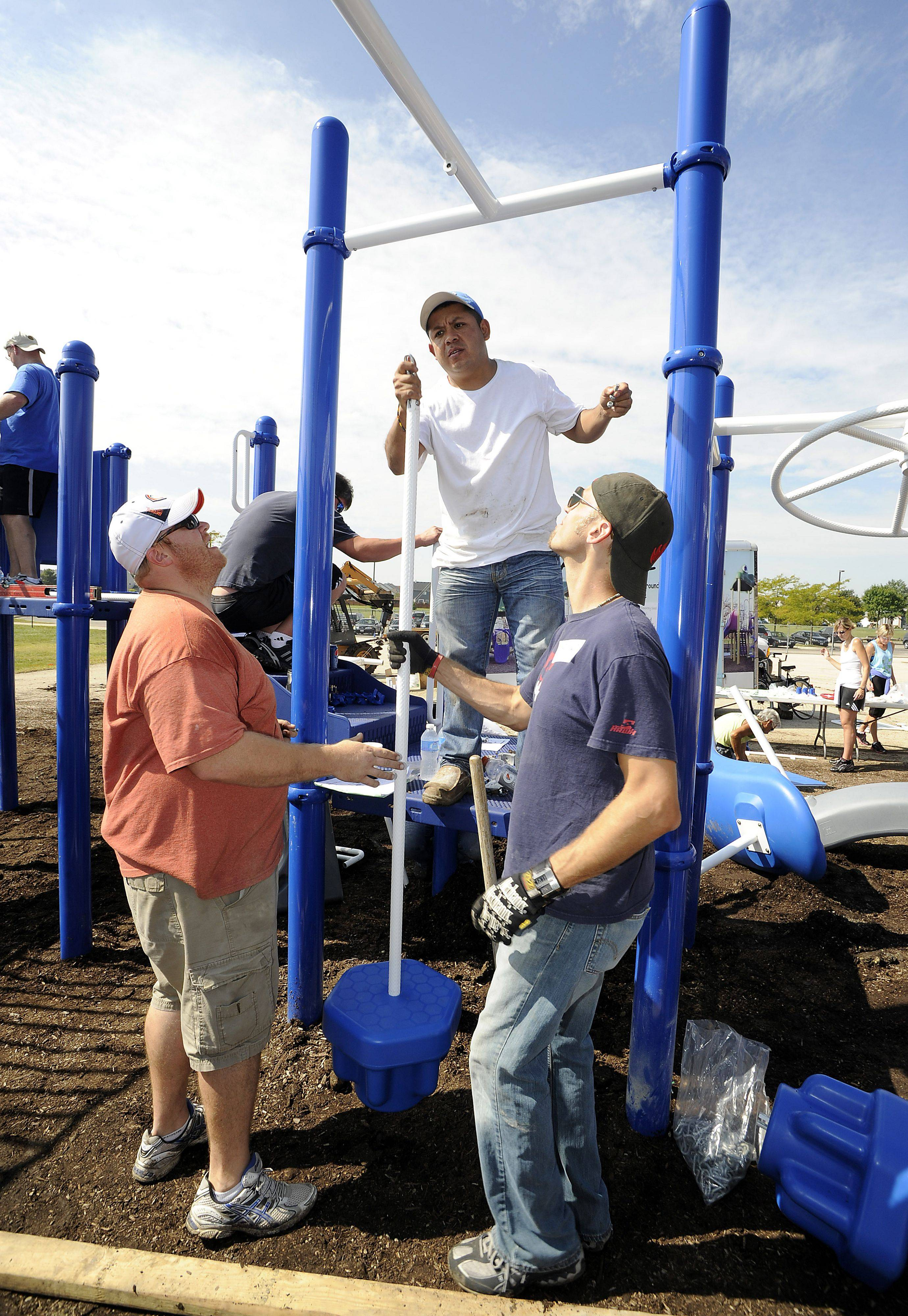 Parents and workers like Jeremy Jahnke, Humberto Lopez and Bob Skwarek work together to assembly a new playground Saturday at the Nature Ridge Elementary School in Bartlett.